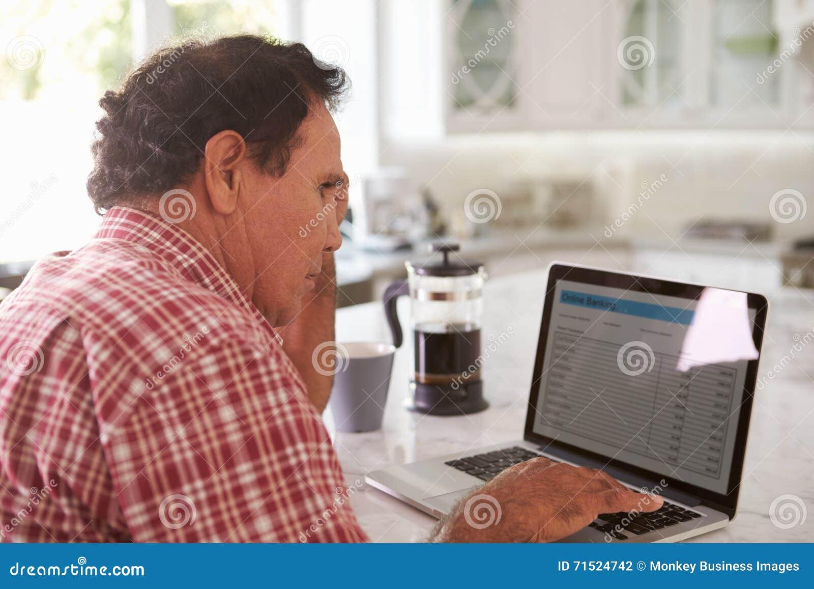 Homme hispanique supérieur confus s asseyant à la maison utilisant l ordinateur portable