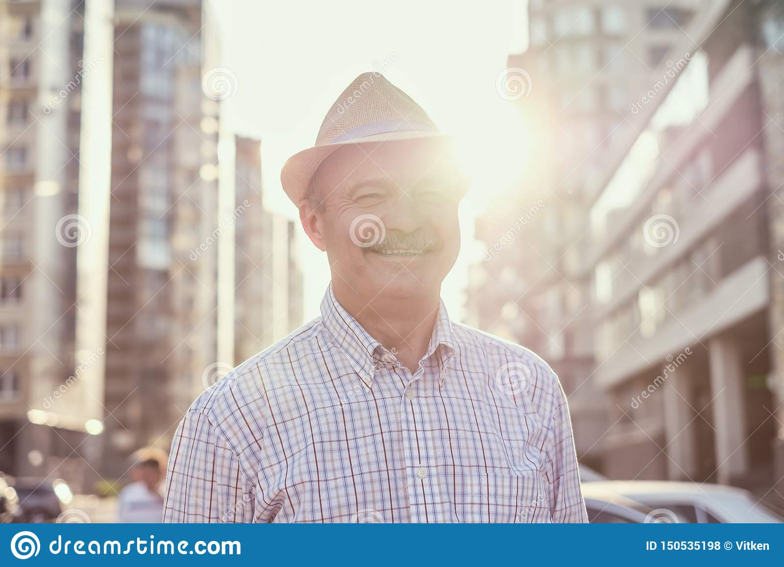 Homme hispanique supérieur retiré avec le chapeau se tenant et souriant