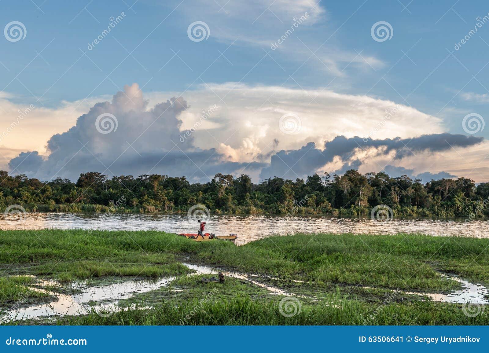 Homme inconnu sur la berge, près du village Coucher du soleil, fin de jour Le 26 juin 2012 dans le village, la Nouvelle-Guinée, I