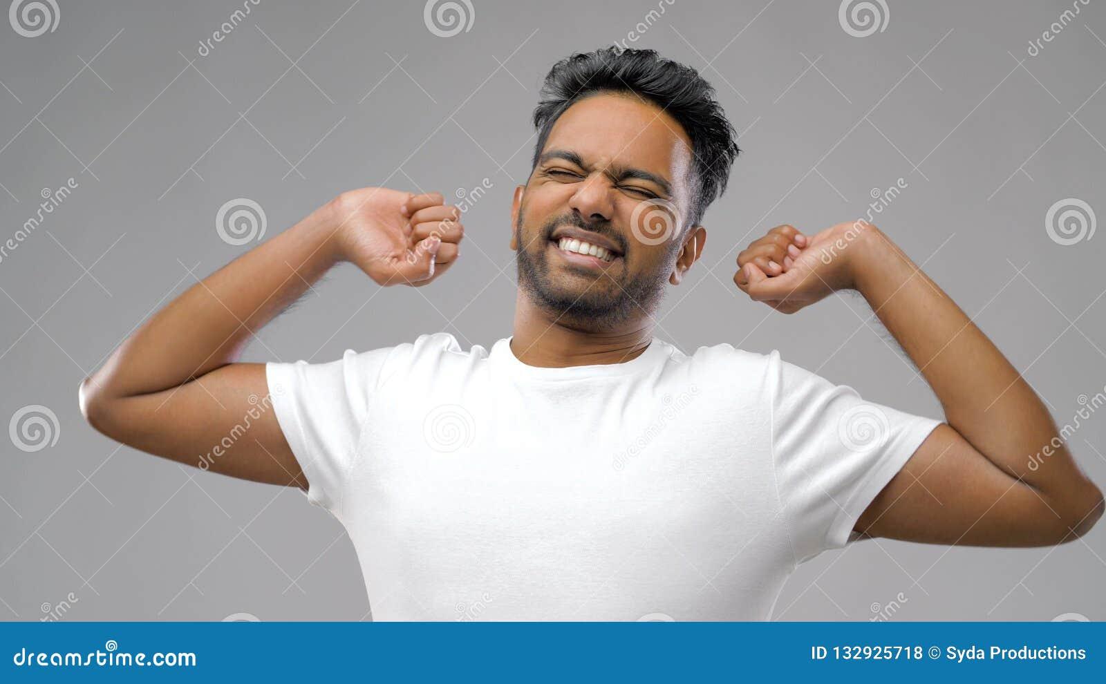 Homme indien s étirant au-dessus du fond gris