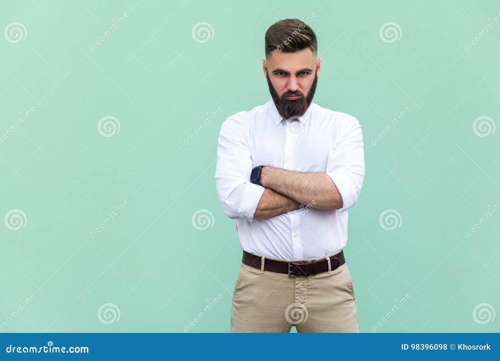 Homme irrité, avec des bras pliés, au-dessus du fond vert clair dans le tir de studio