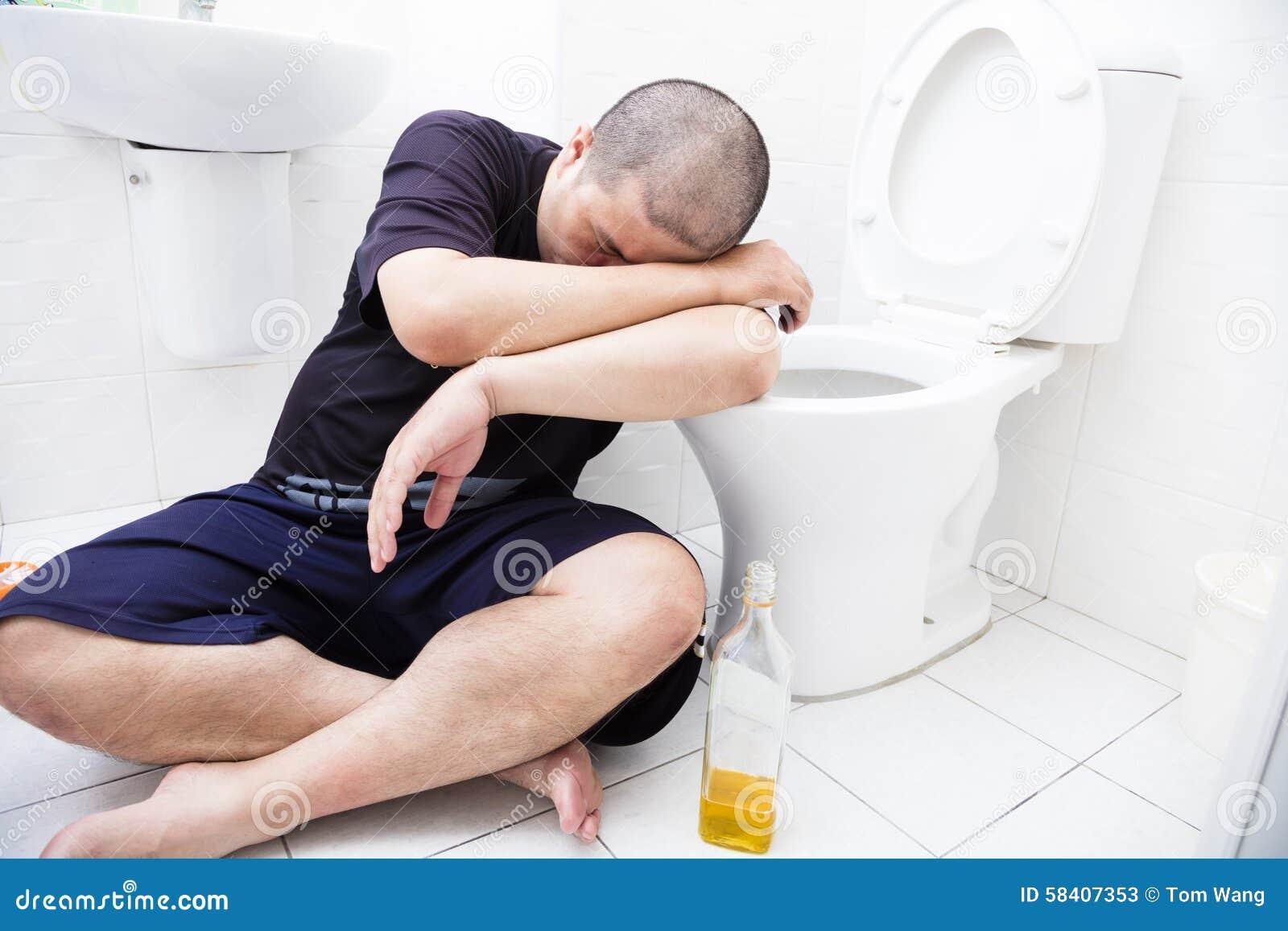 Homme ivre avec la bouteille de vin dans la toilette