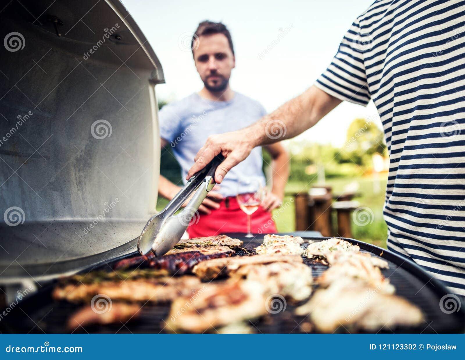 Homme méconnaissable faisant cuire des fruits de mer sur un gril de barbecue dans l arrière-cour Fin vers le haut