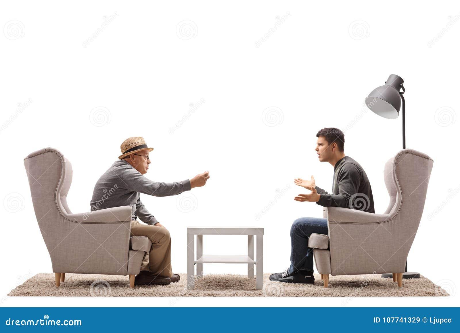Homme mûr et jeune un type assis dans l argumentation de fauteuils
