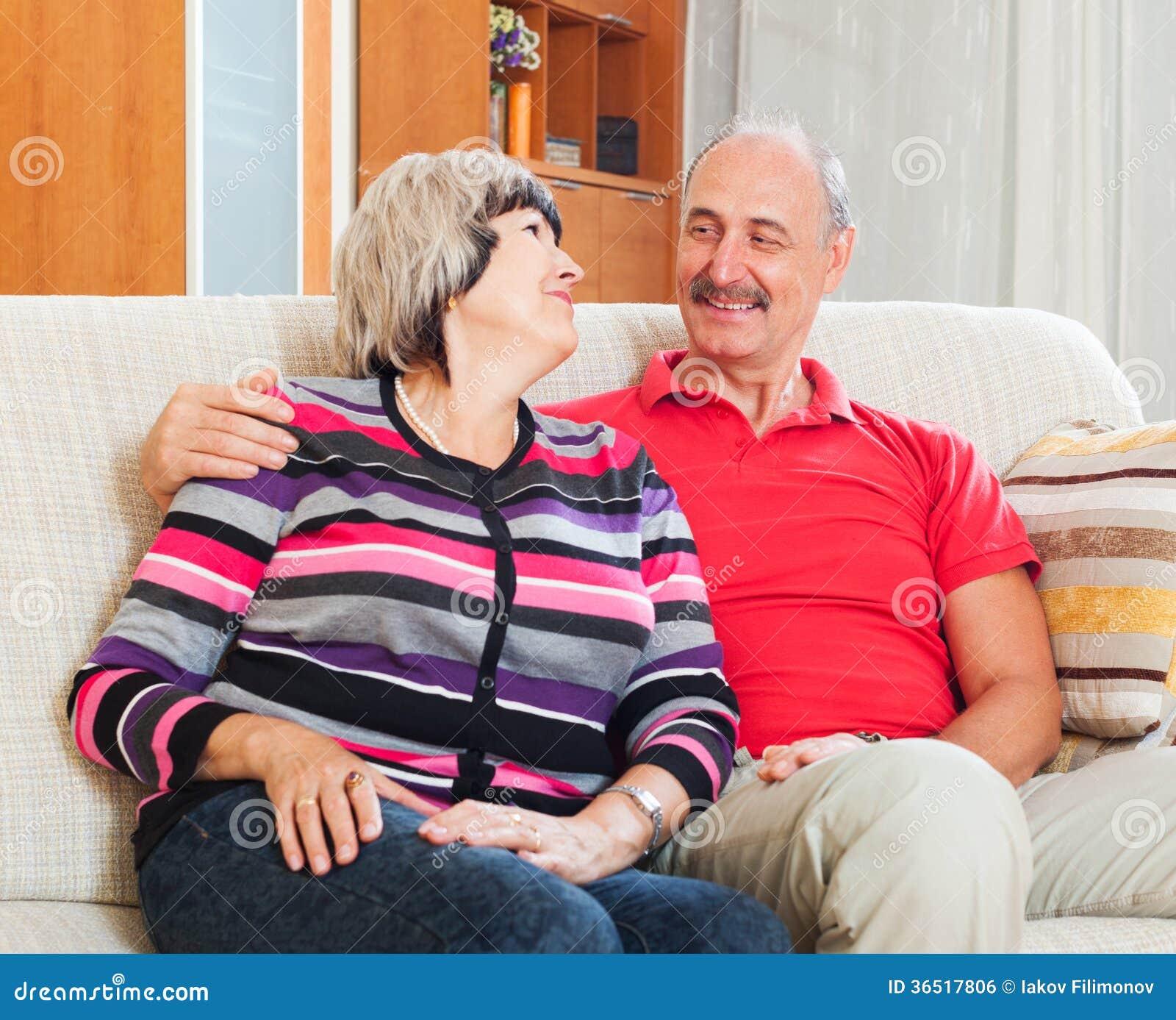 Homme mûr de sourire avec l épouse dans la maison