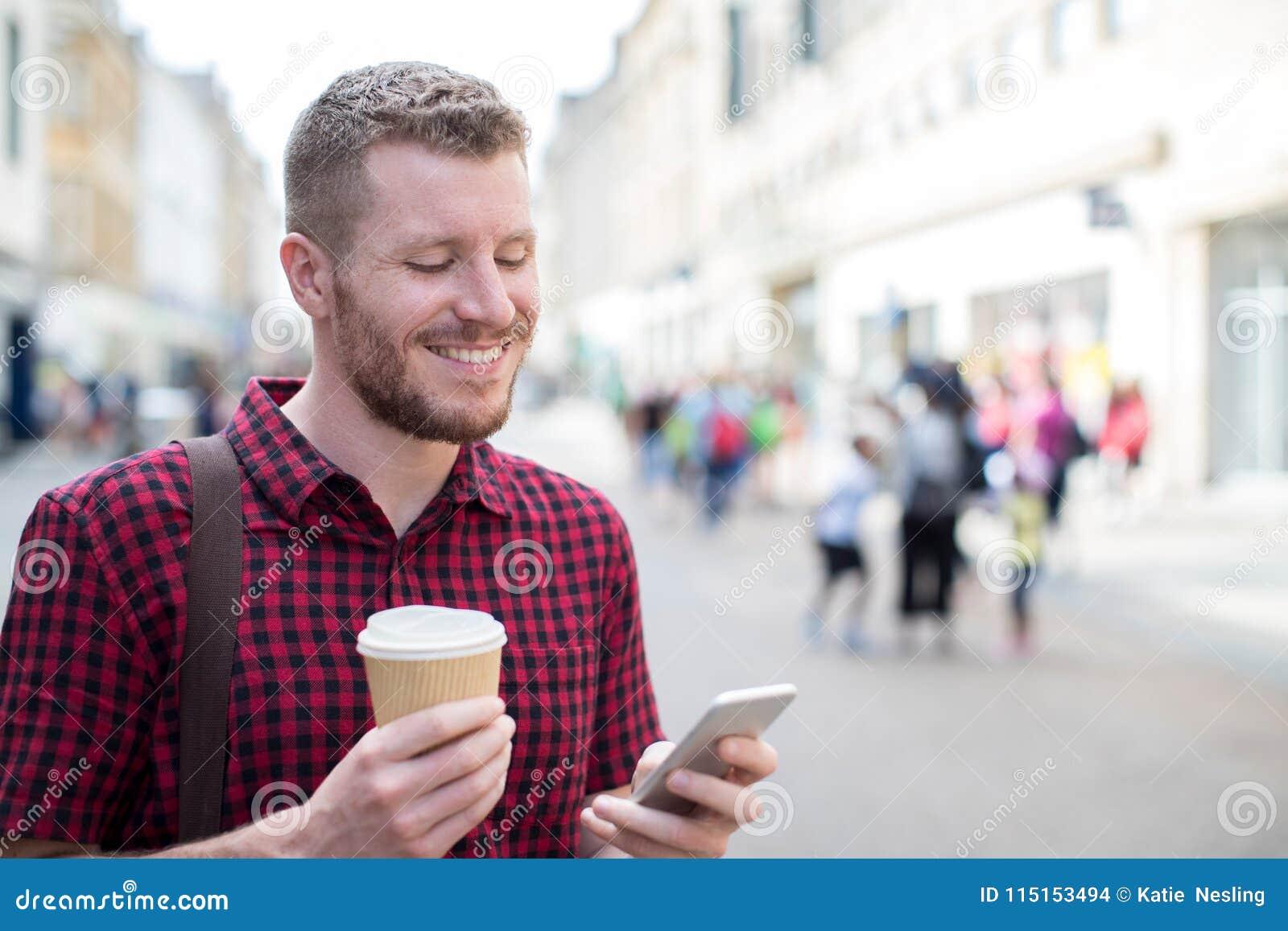 Homme marchant le long du message textuel de lecture de rue de ville sur Pho mobile