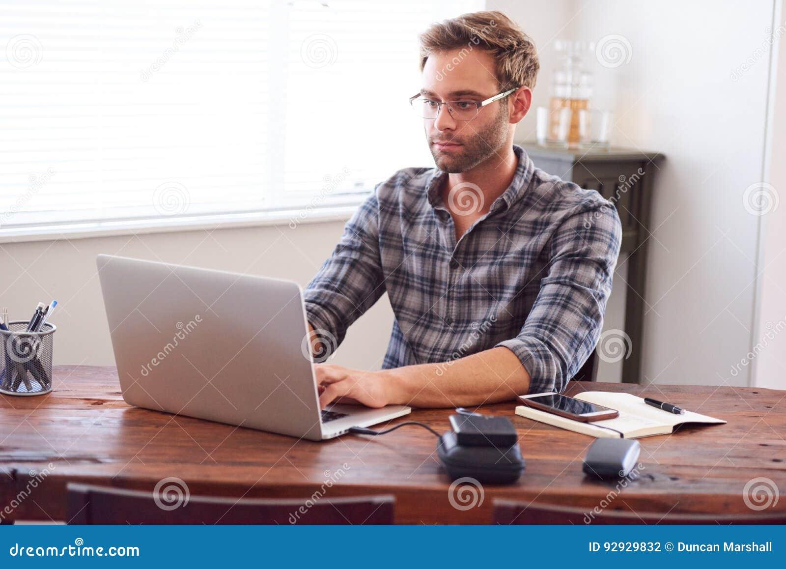 Homme moderne dactylographiant sur un ordinateur portable tandis