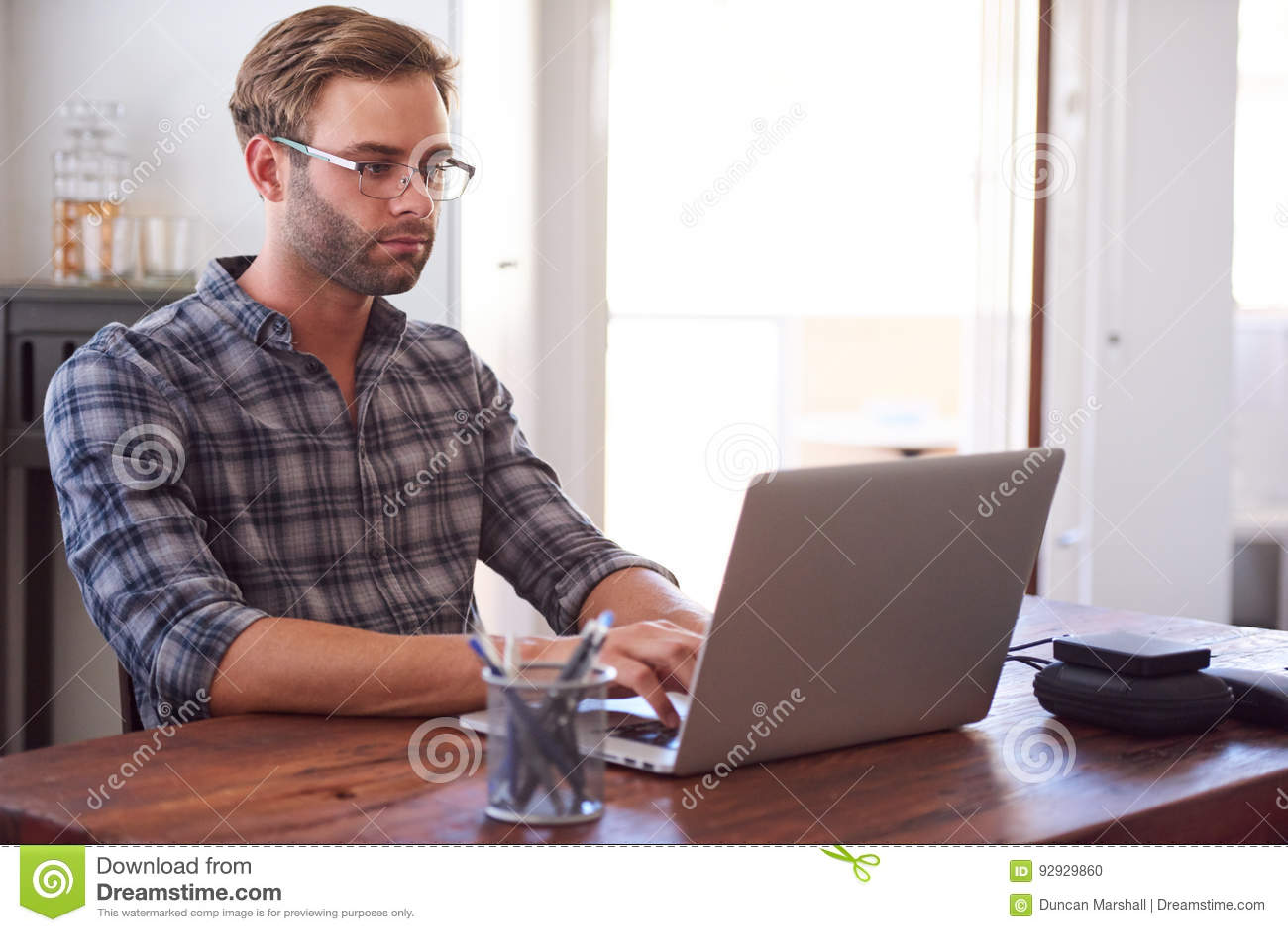 Homme moderne dactylographiant sur un ordinateur portable tandis qu