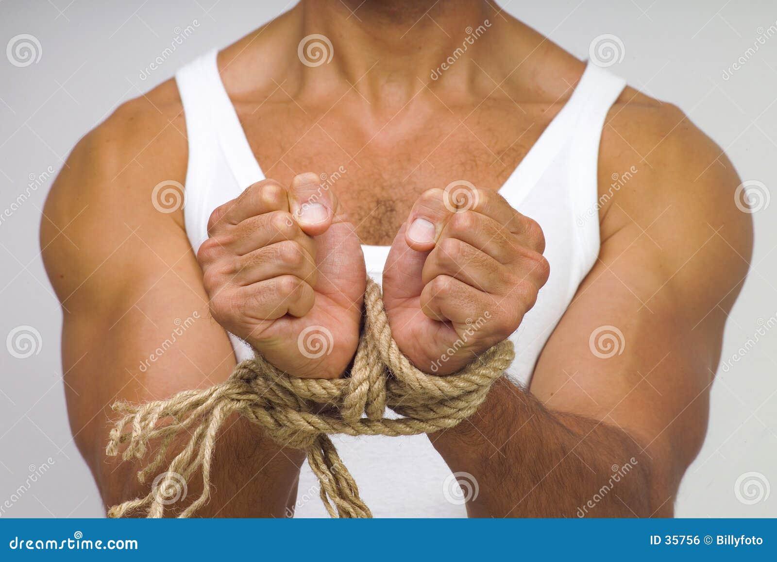 Homme musculaire avec des mains attachées par la corde