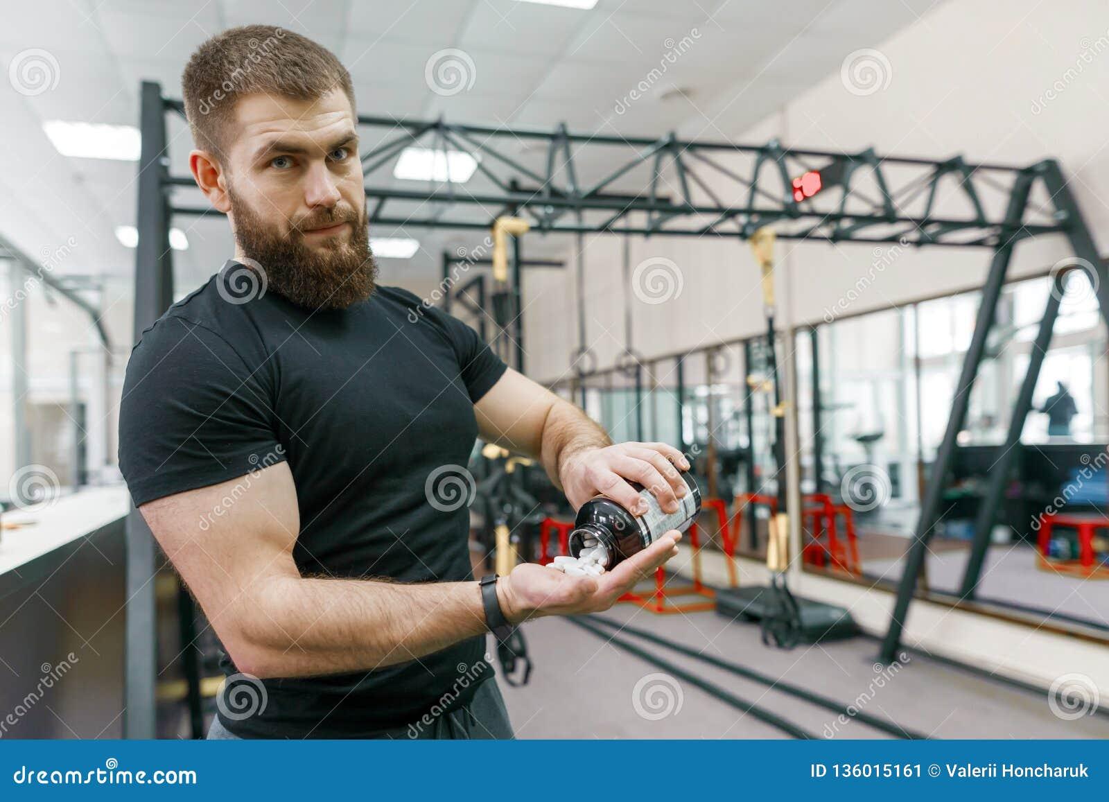 Homme musculaire sportif montrant des sports et des suppléments de forme physique, capsules, pilules, fond de gymnase Mode de vie