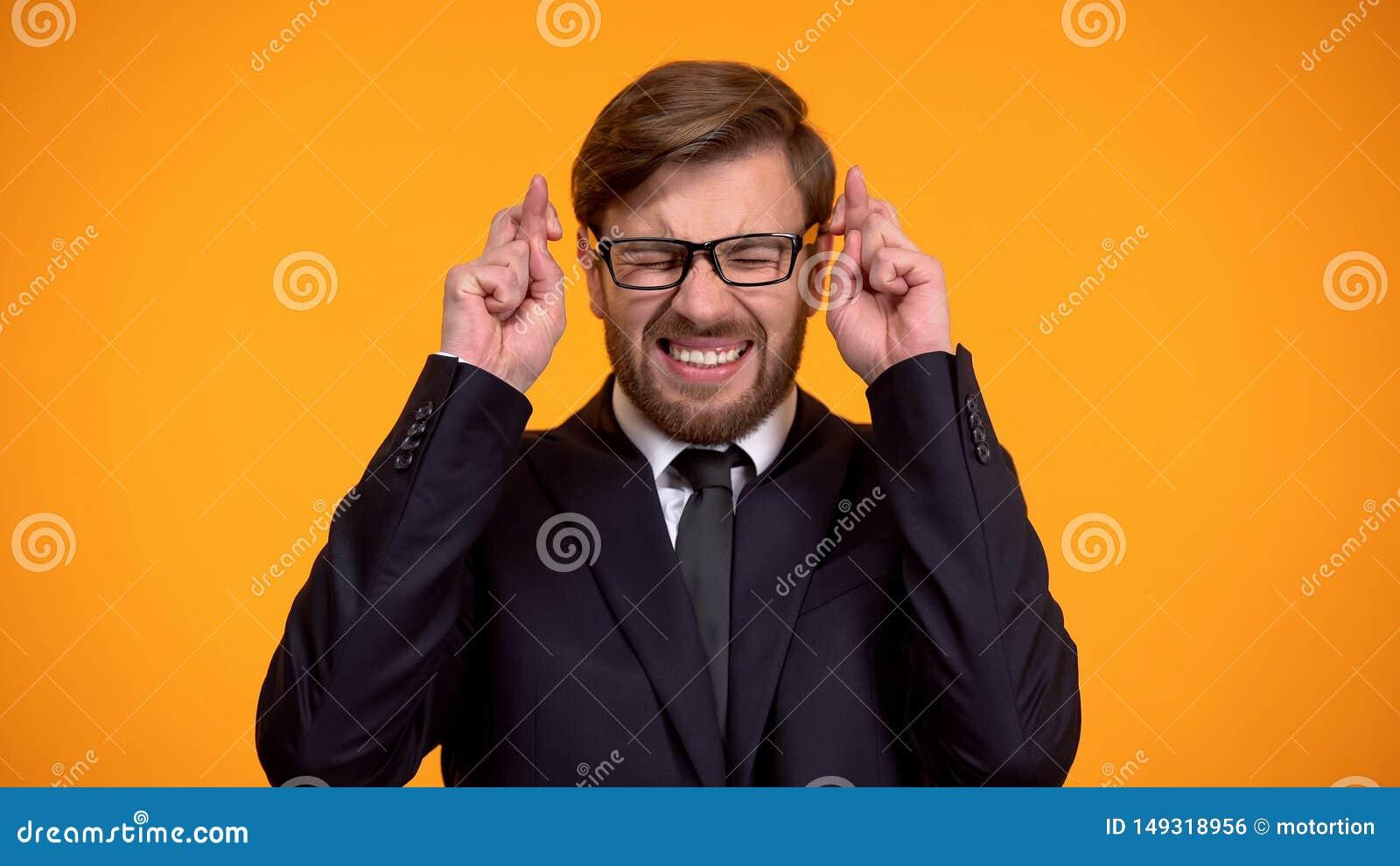 Homme nerveux dans des doigts de croisement de costume pour la bonne chance, esp?rant gagner