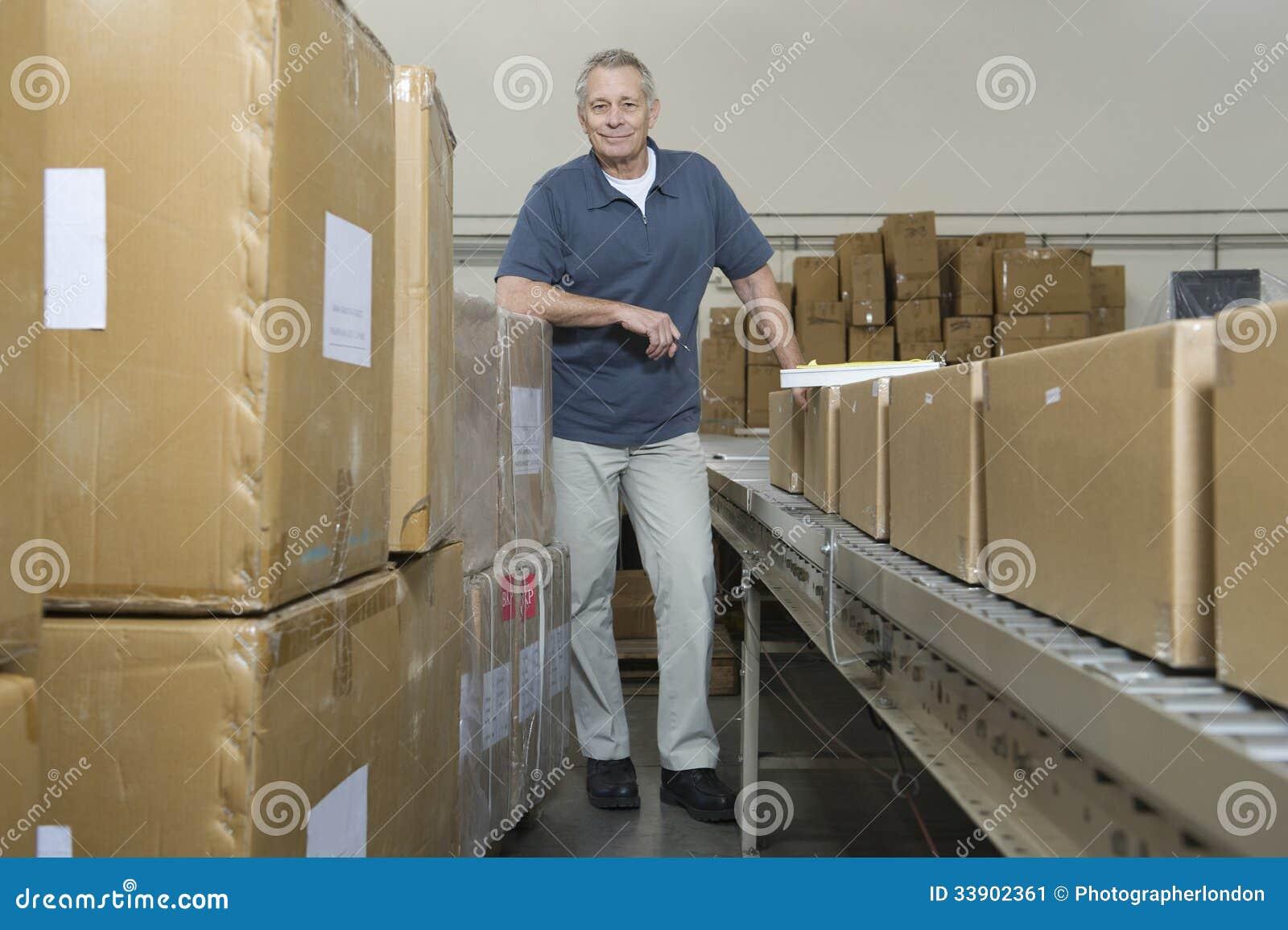 Homme par la bande de conveyeur et les boîtes dans l entrepôt
