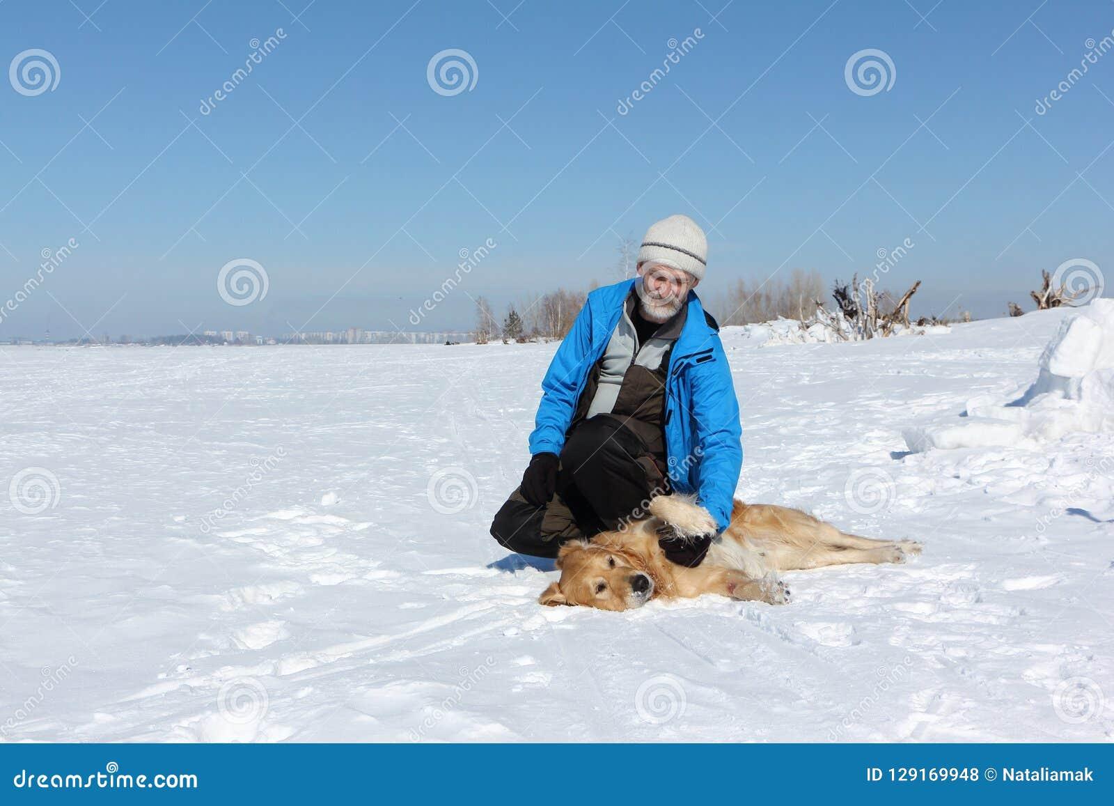 Homme plus âgé dans une veste bleue et un chien un Labrador sur la neige