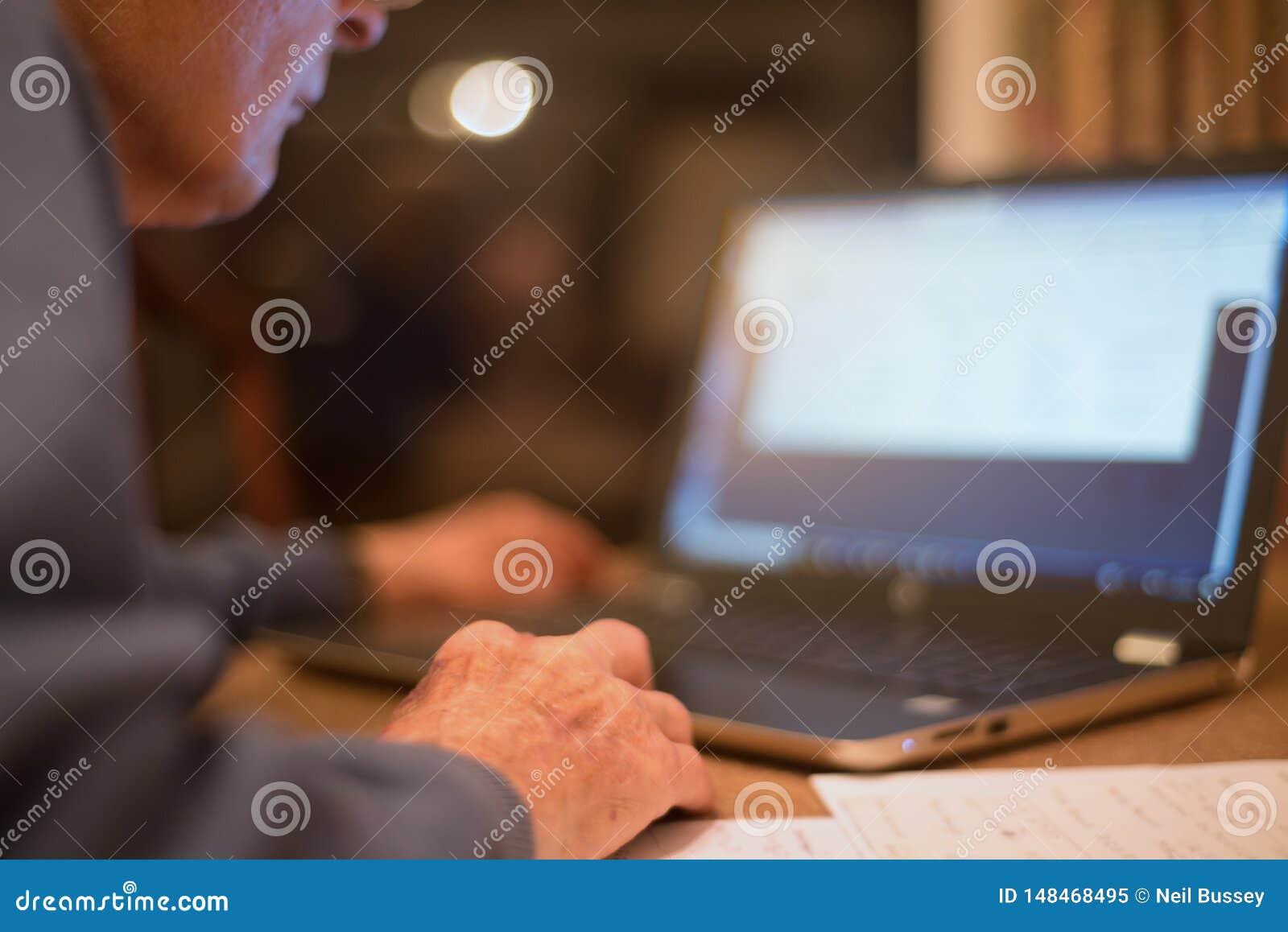Homme plus ?g? utilisant un ordinateur portable pour v?rifier ses portefeuilles d actions, Hampshire, Angleterre, U k