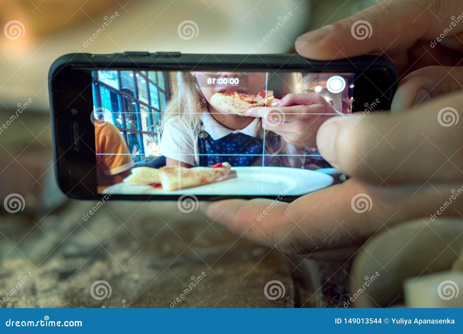 Homme prenant la photo d une fille mangeant de la pizza