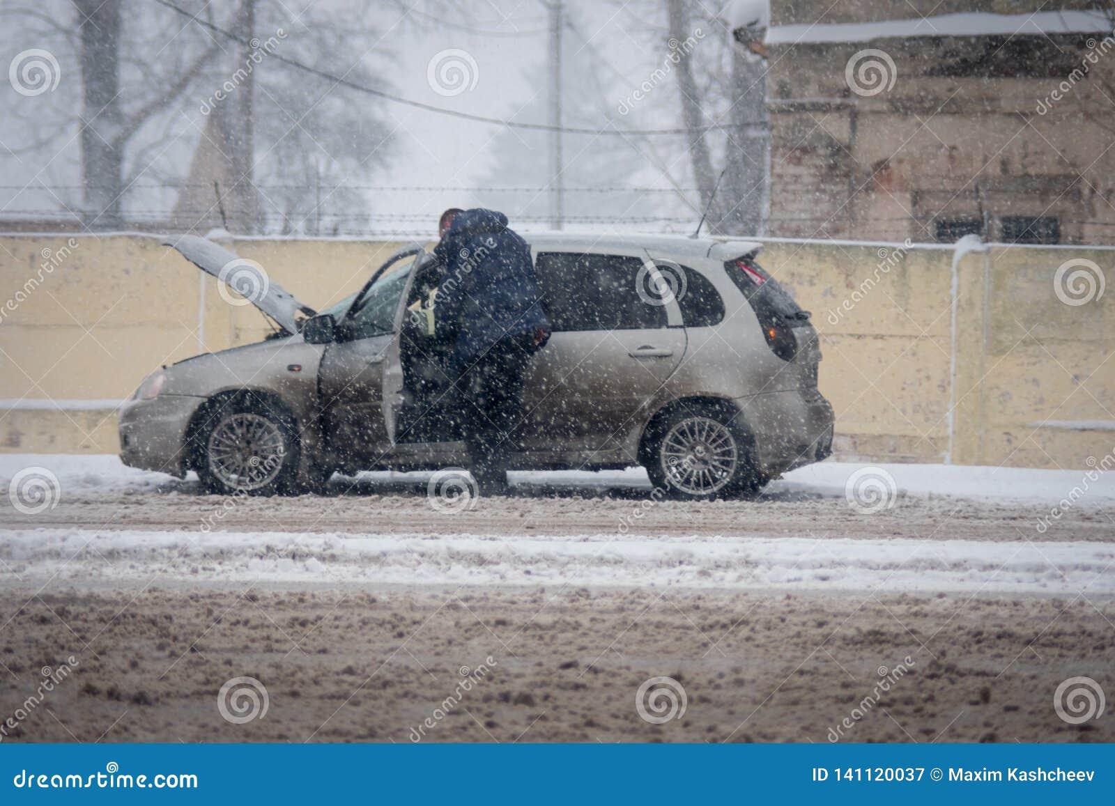 Homme réparant la voiture cassée sur la route en chutes de neige