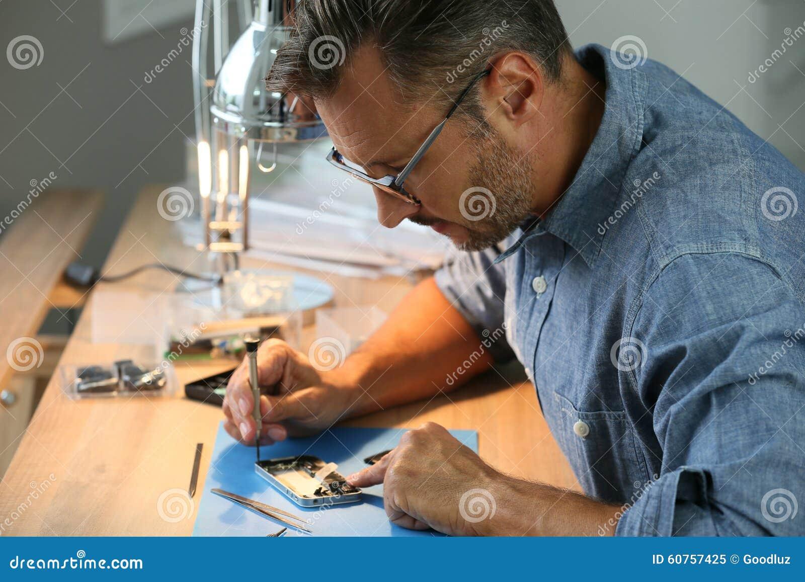 Homme réparant le smartphone dans l atelier