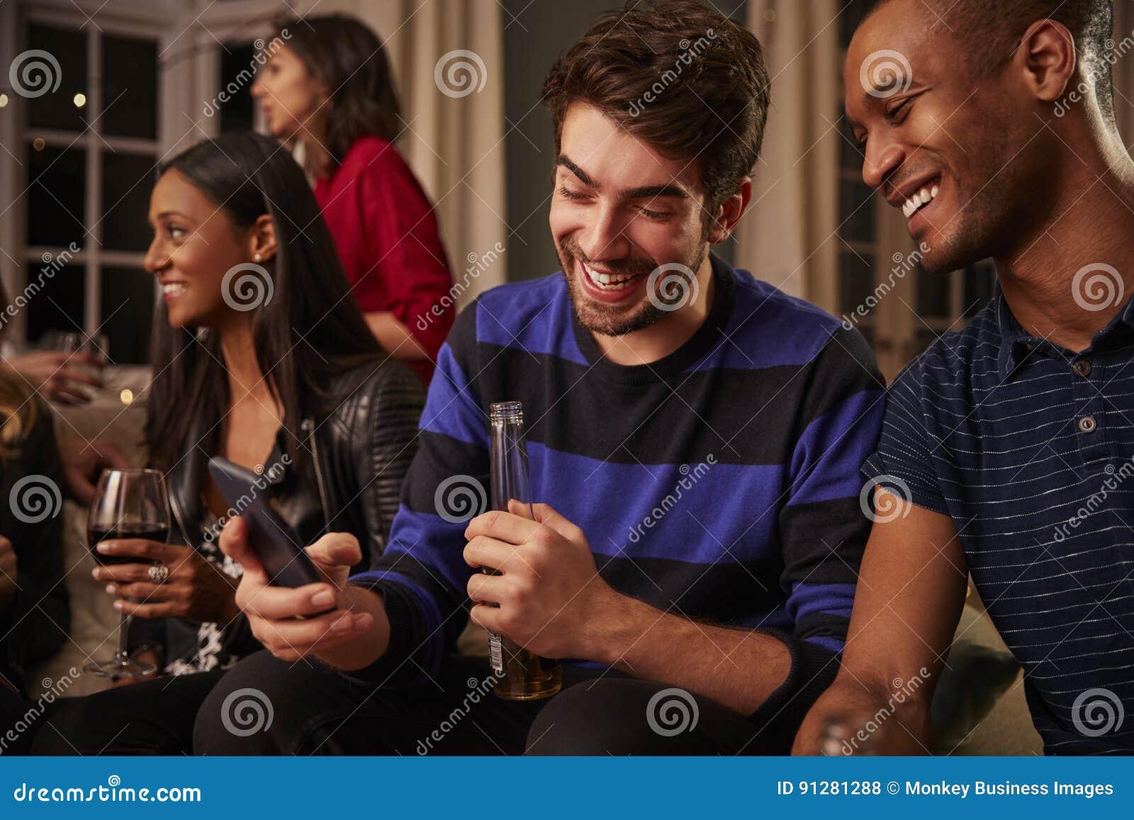 Homme regardant le message au téléphone portable la partie