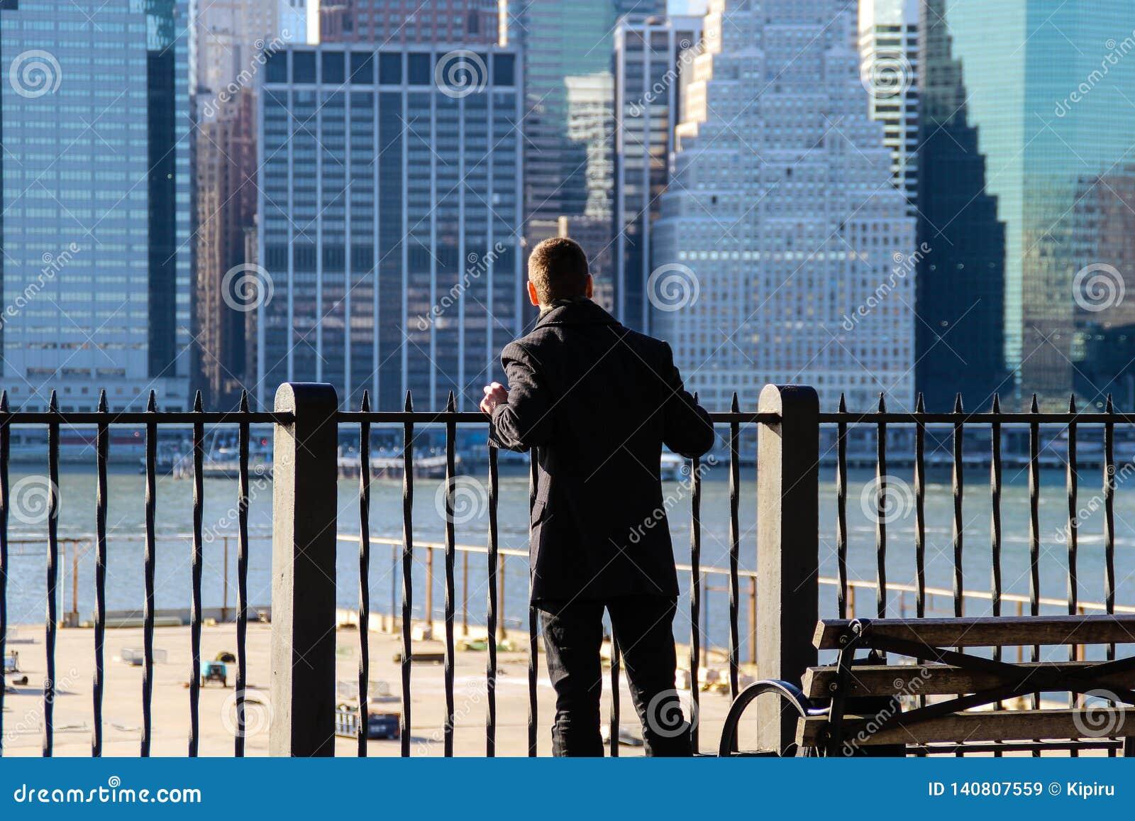 Homme regardant sur Manhattan de Brooklyn