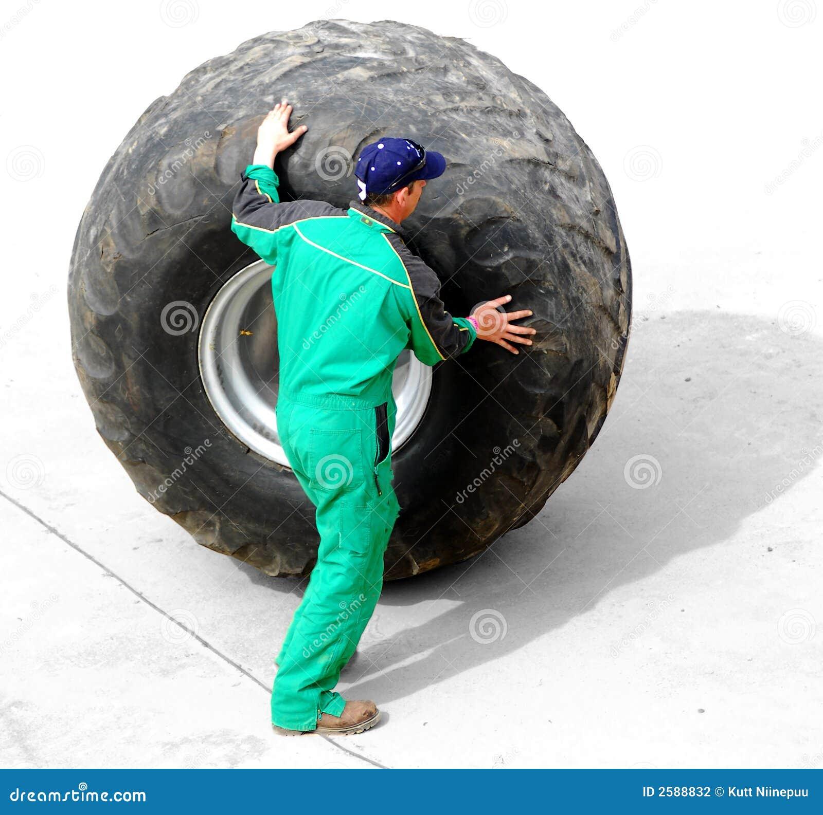 Homme roulant la roue énorme de camion