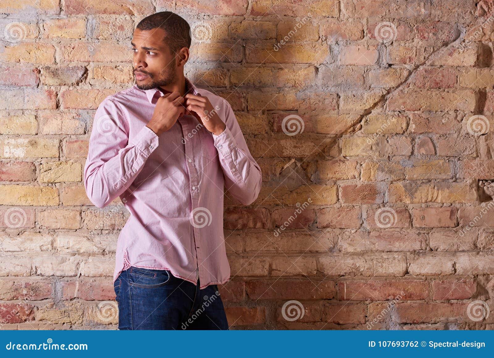 Homme sérieux boutonnant la chemise