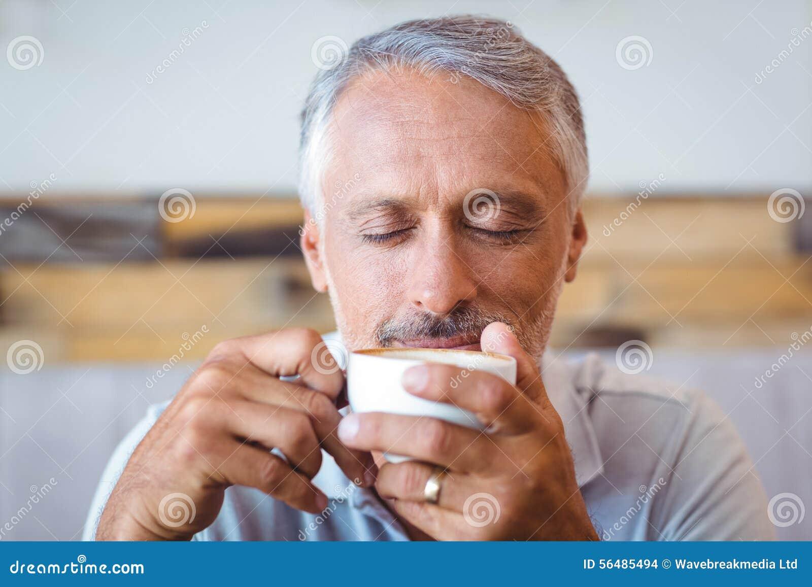 Homme s asseyant en café ayant le café