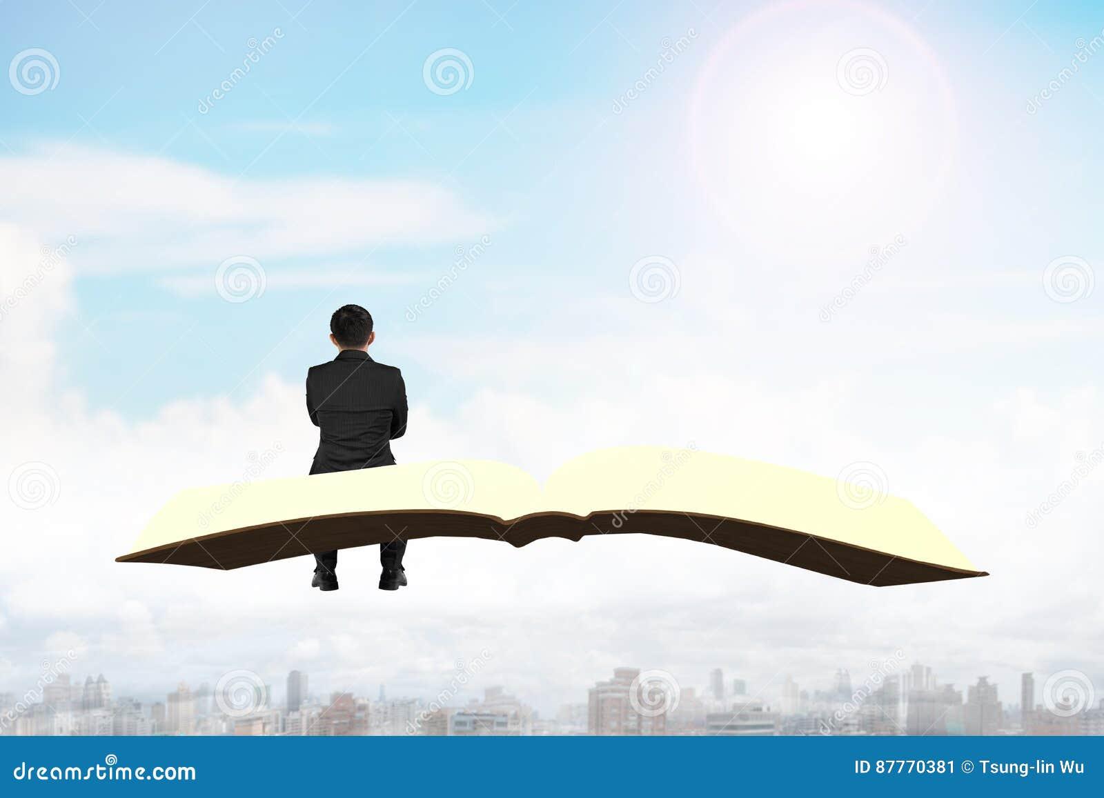 Homme S Asseyant Sur Le Livre Volant Au Dessus De La Ville