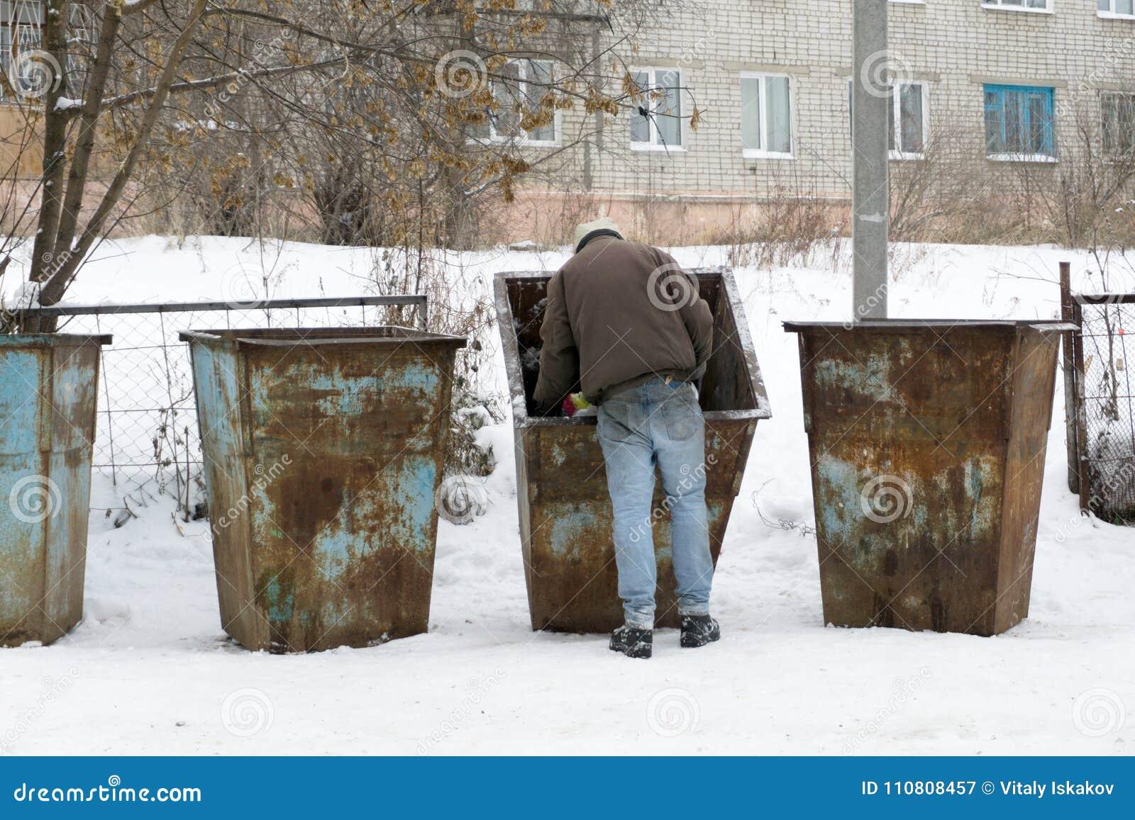 Homme sans abri sale tenant l emballage pour des oeufs, se tenant prêt la poubelle Mode de vie de bruit de pas, vivant dans les r
