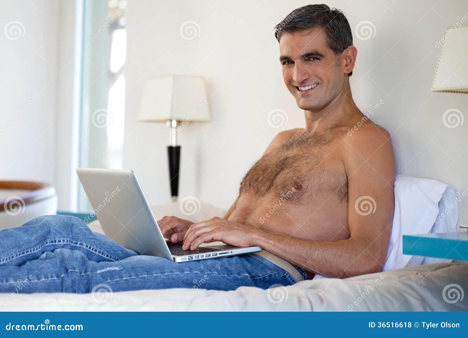 Homme sans chemise travaillant sur l ordinateur portable