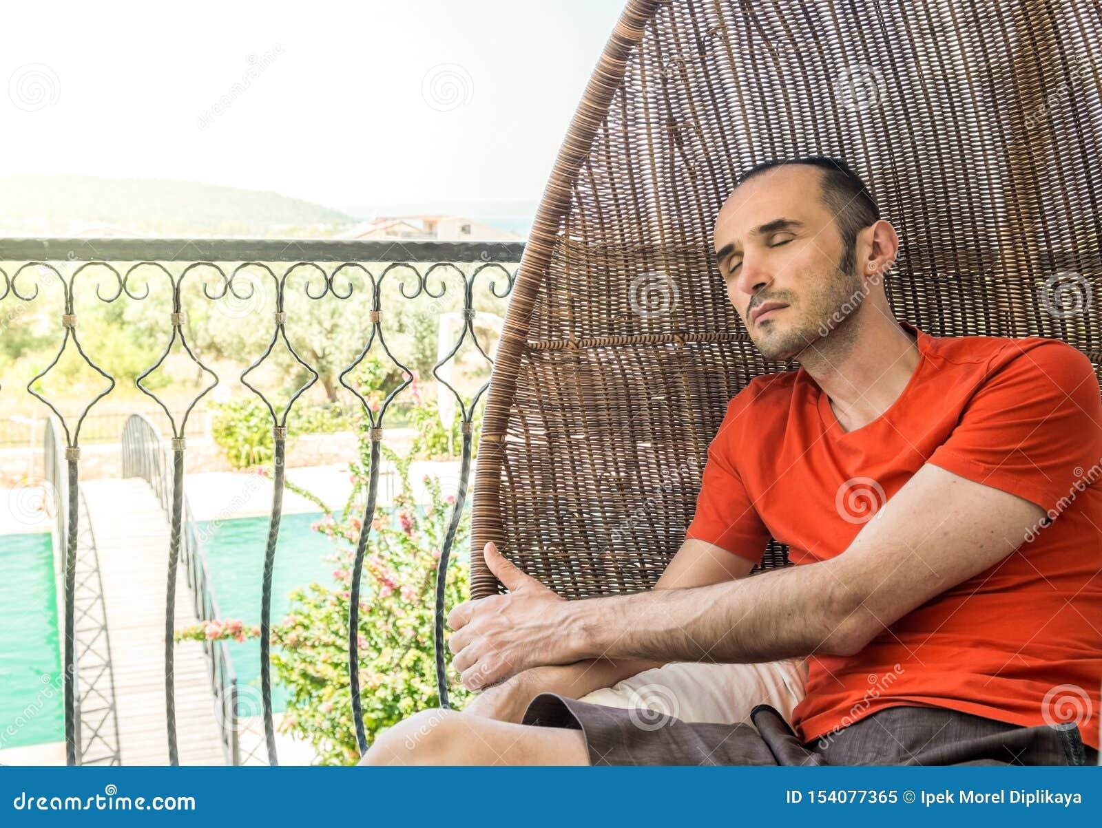 Homme se reposant pour détendre sur la chaise de oscillation dans un balcon