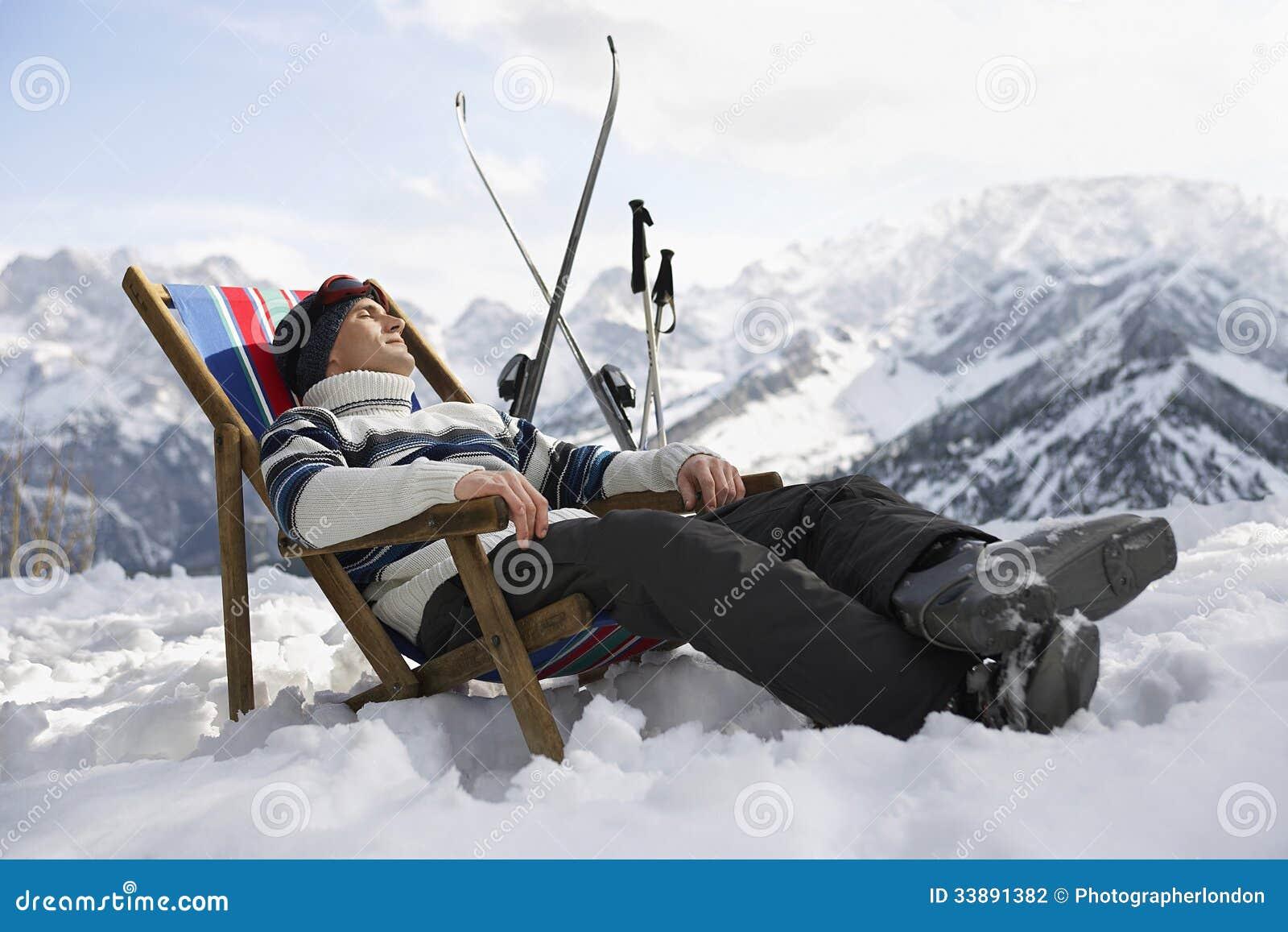 homme se reposant sur la chaise longue en montagnes de milou photo stock image du people. Black Bedroom Furniture Sets. Home Design Ideas