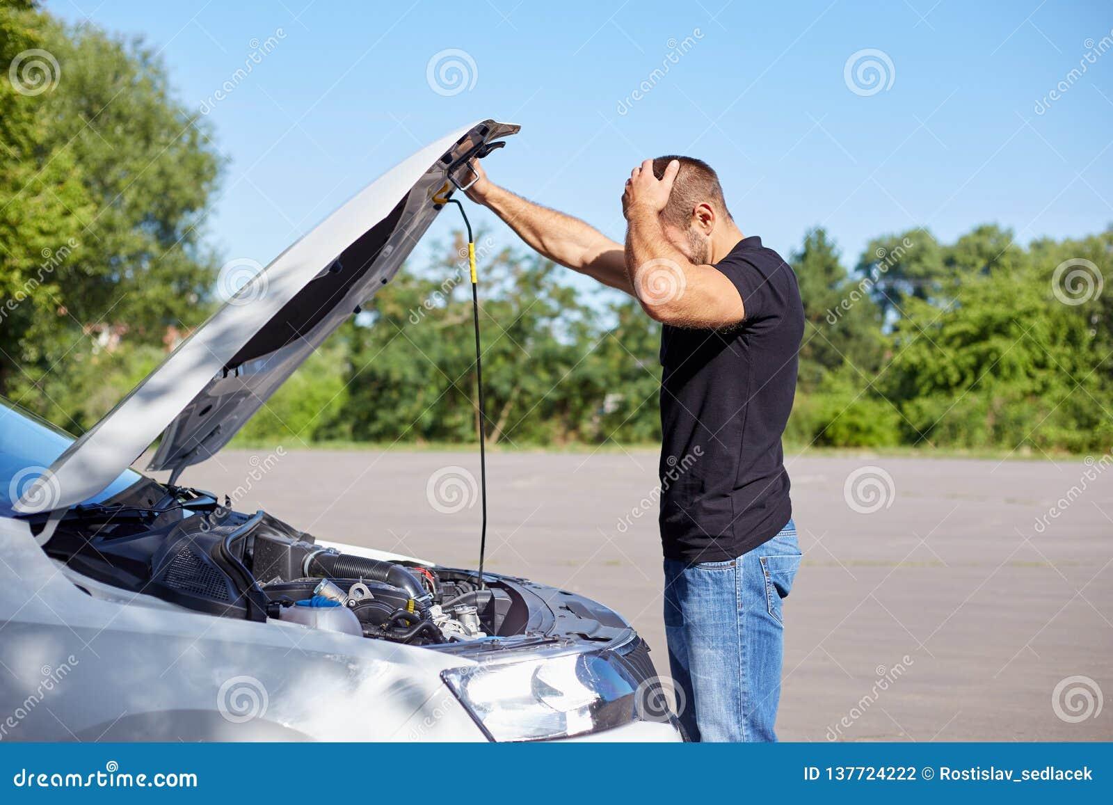 Homme se tenant devant une voiture cassée