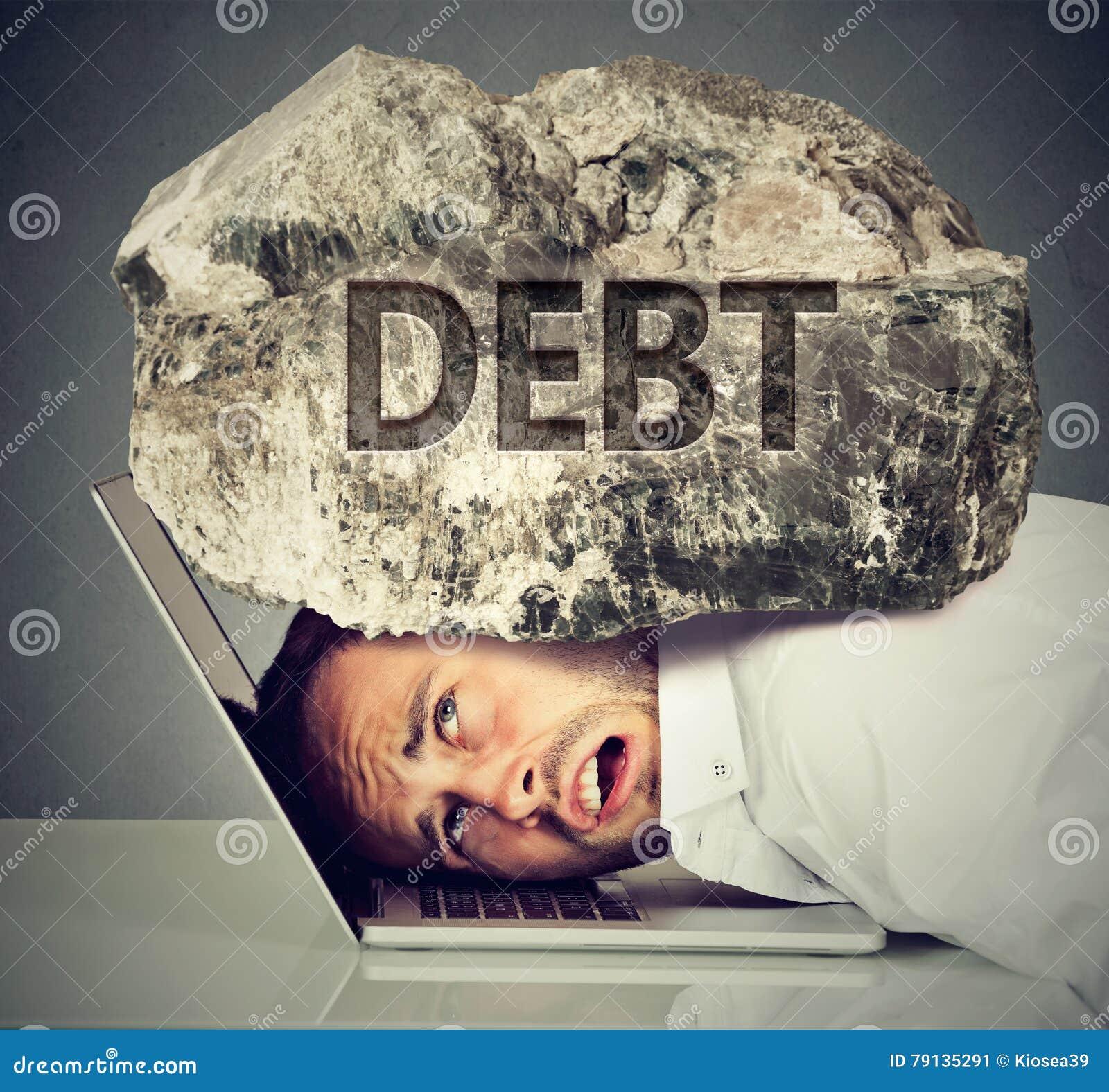 Homme serré entre l ordinateur portable et la roche Concept de dette d emprunt d étudiant
