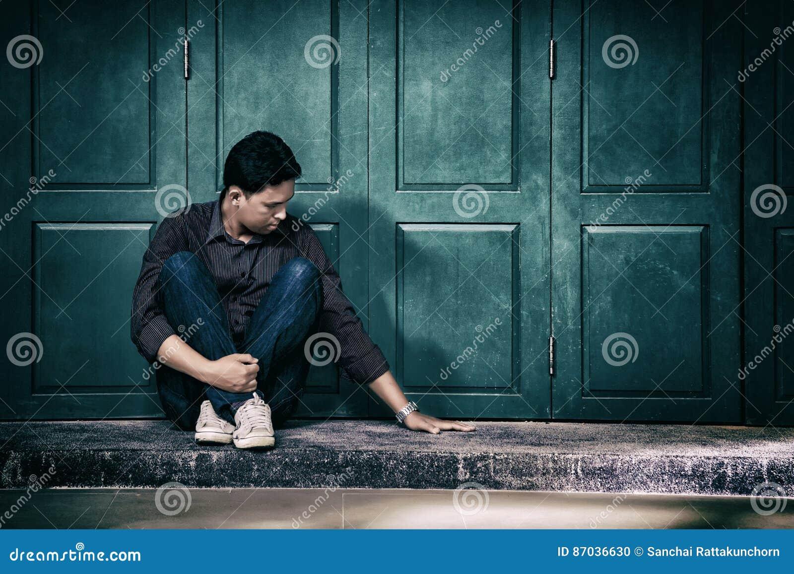 Homme seul bel dans la dépression frustrante seul se reposant sur le Th