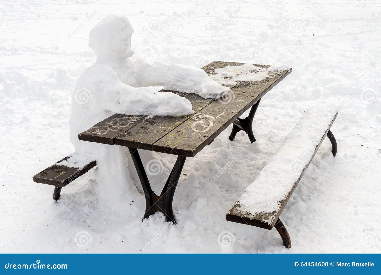 Homme seul de neige s asseyant à la table de pique-nique