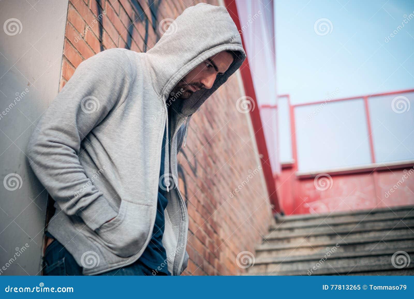 Homme seul se penchant contre un mur urbain