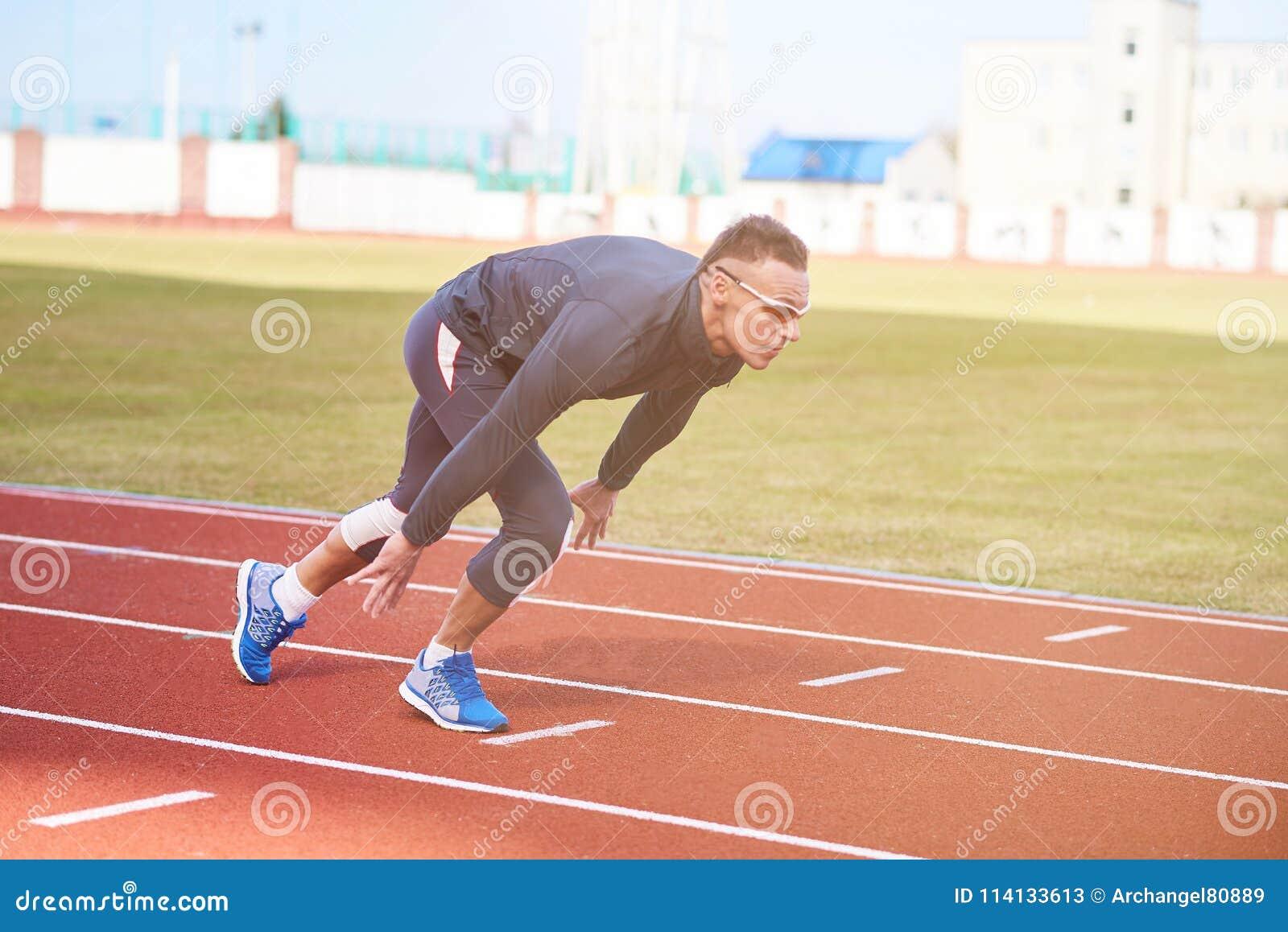 Homme sportif bel au début du tapis roulant de stade