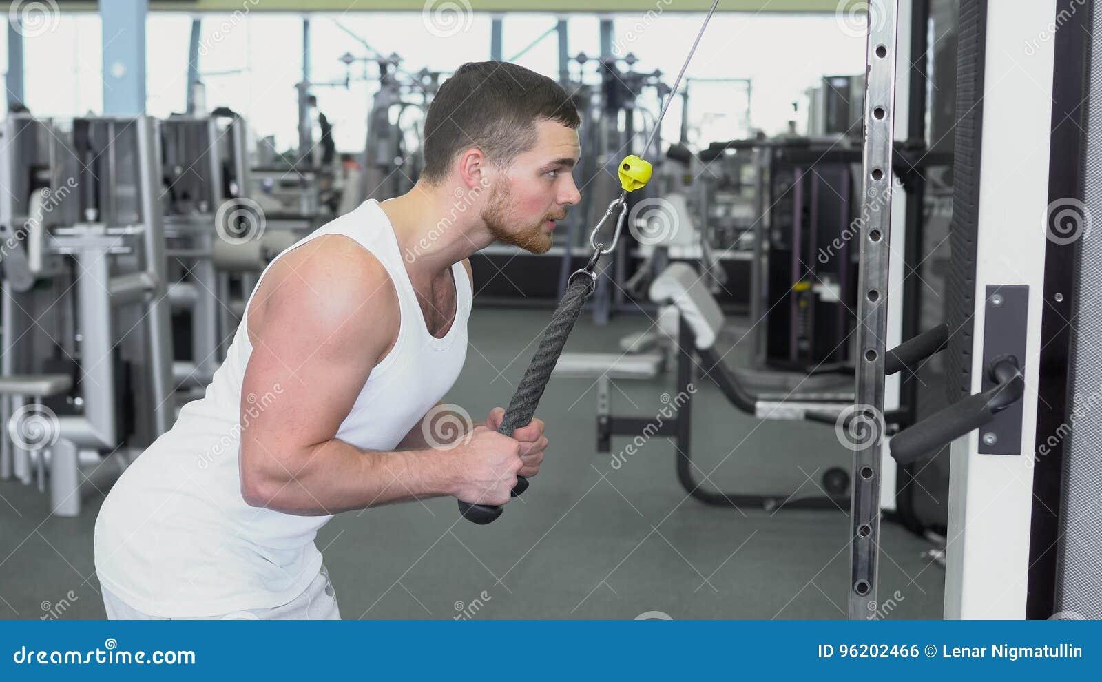 Homme sportif fort dans un T-shirt à la formation de gymnase sur le périphérique en mode bloc Formation de CrossFit