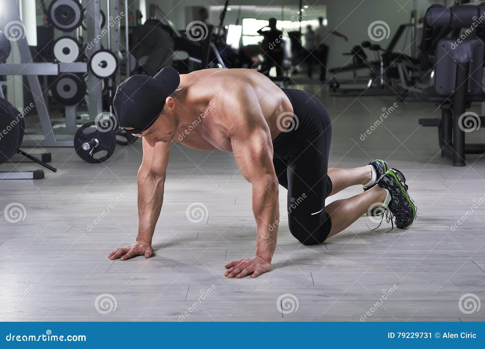 Homme sportif puissant bel se préparant à effectuer des pousées