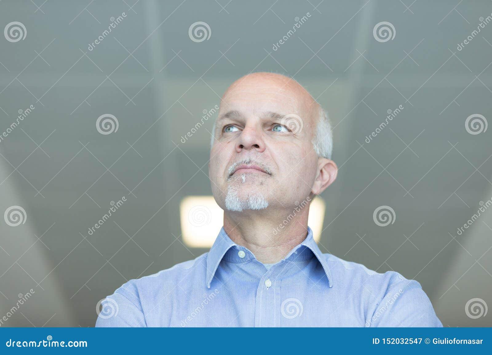 Homme supérieur avec une expression réfléchie lointaine