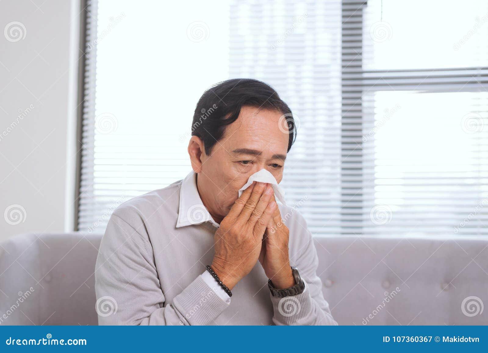 Homme supérieur ayant la grippe, avec le chiffon de papier soufflant son nez