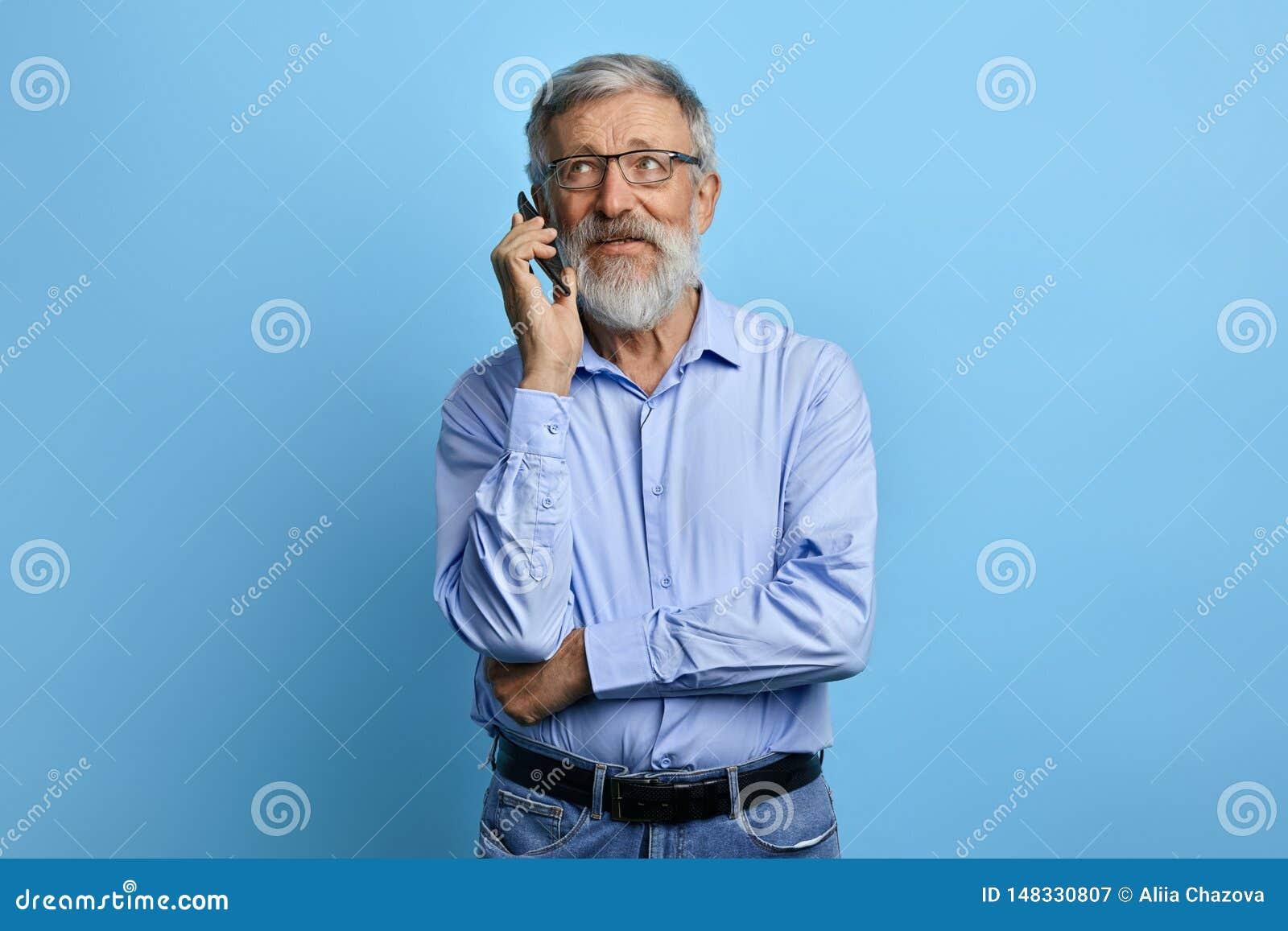 Homme supérieur bel recherchant, parlant au téléphone portable
