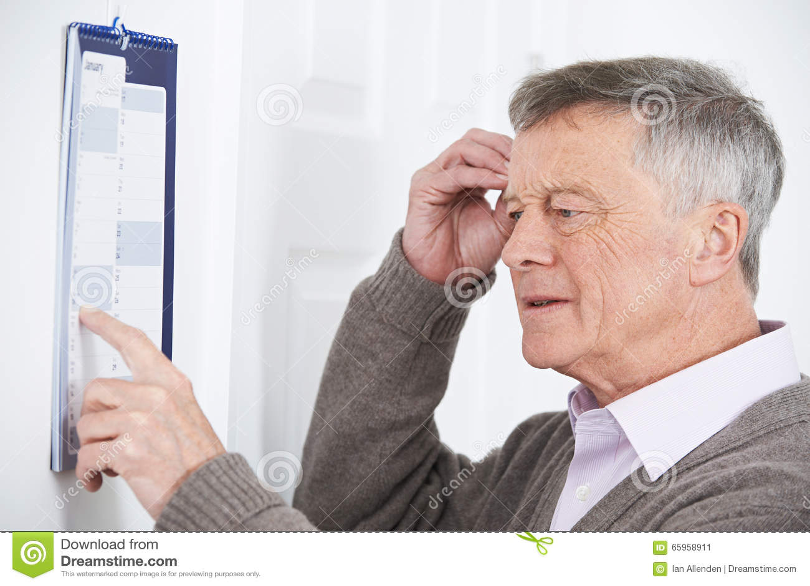 Homme supérieur confus avec la démence regardant le calendrier mural