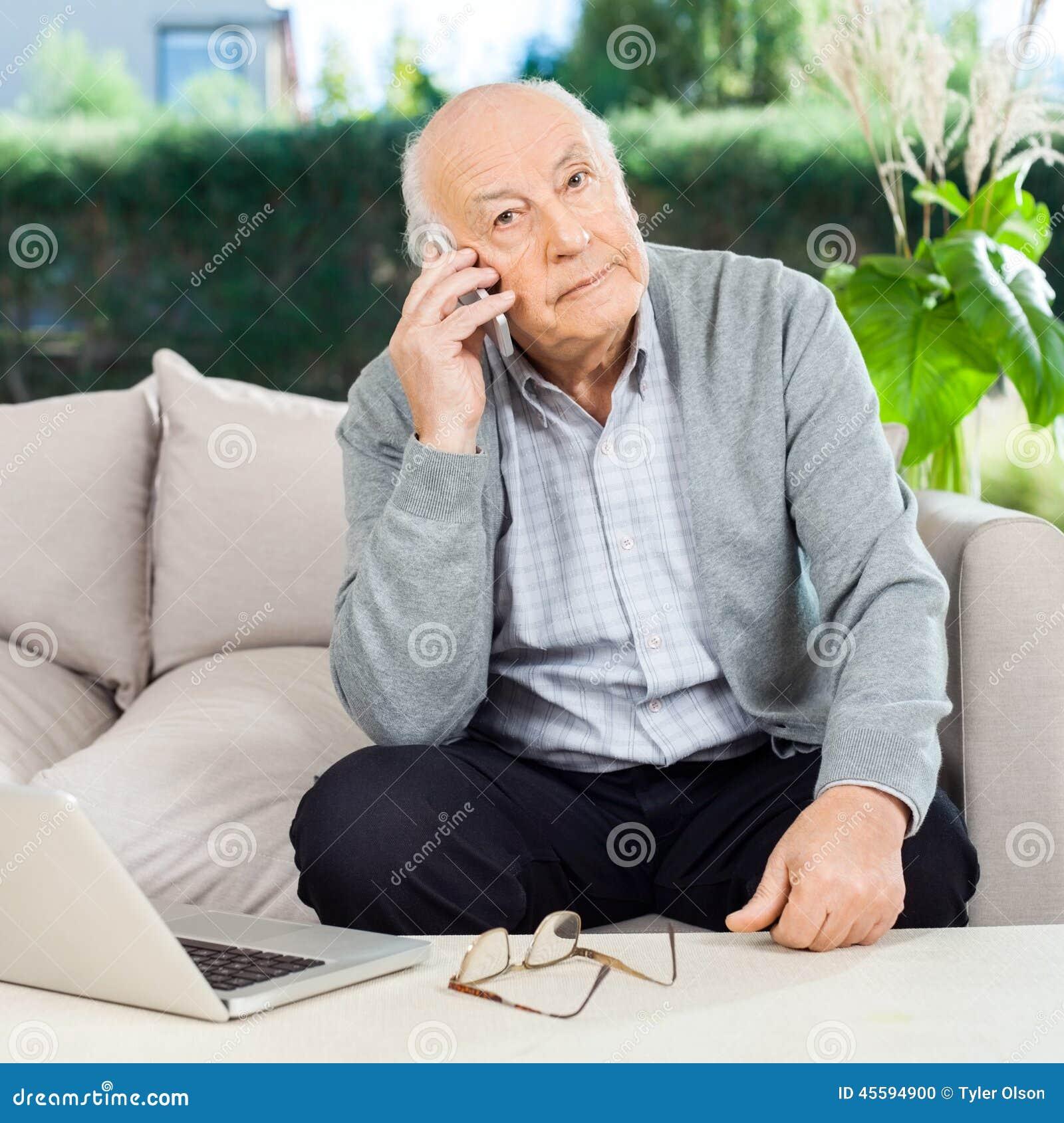 Homme supérieur employant Smartphone au porche de maison de repos