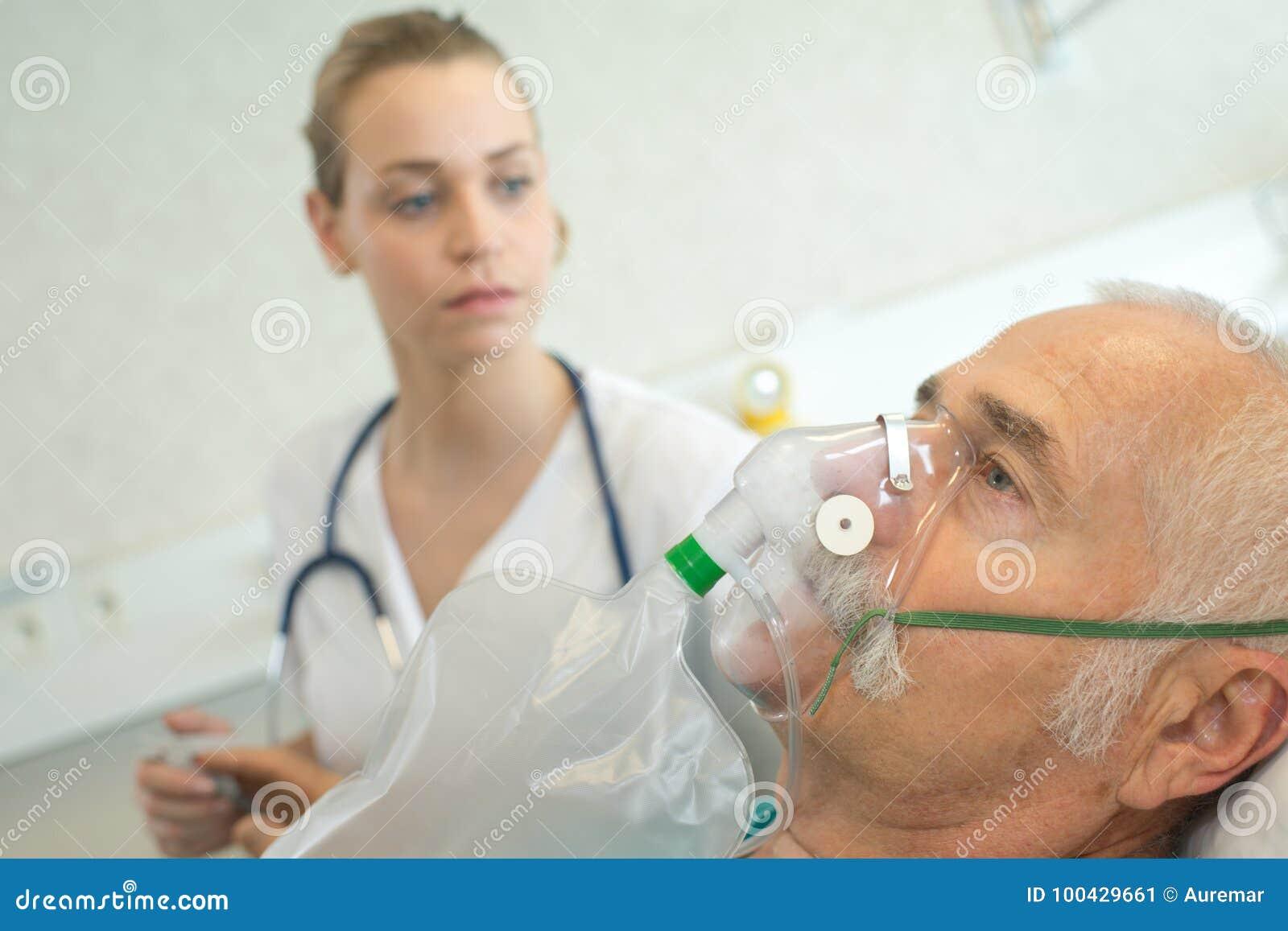 Homme supérieur en gros plan employant le masque à oxygène dans la clinique