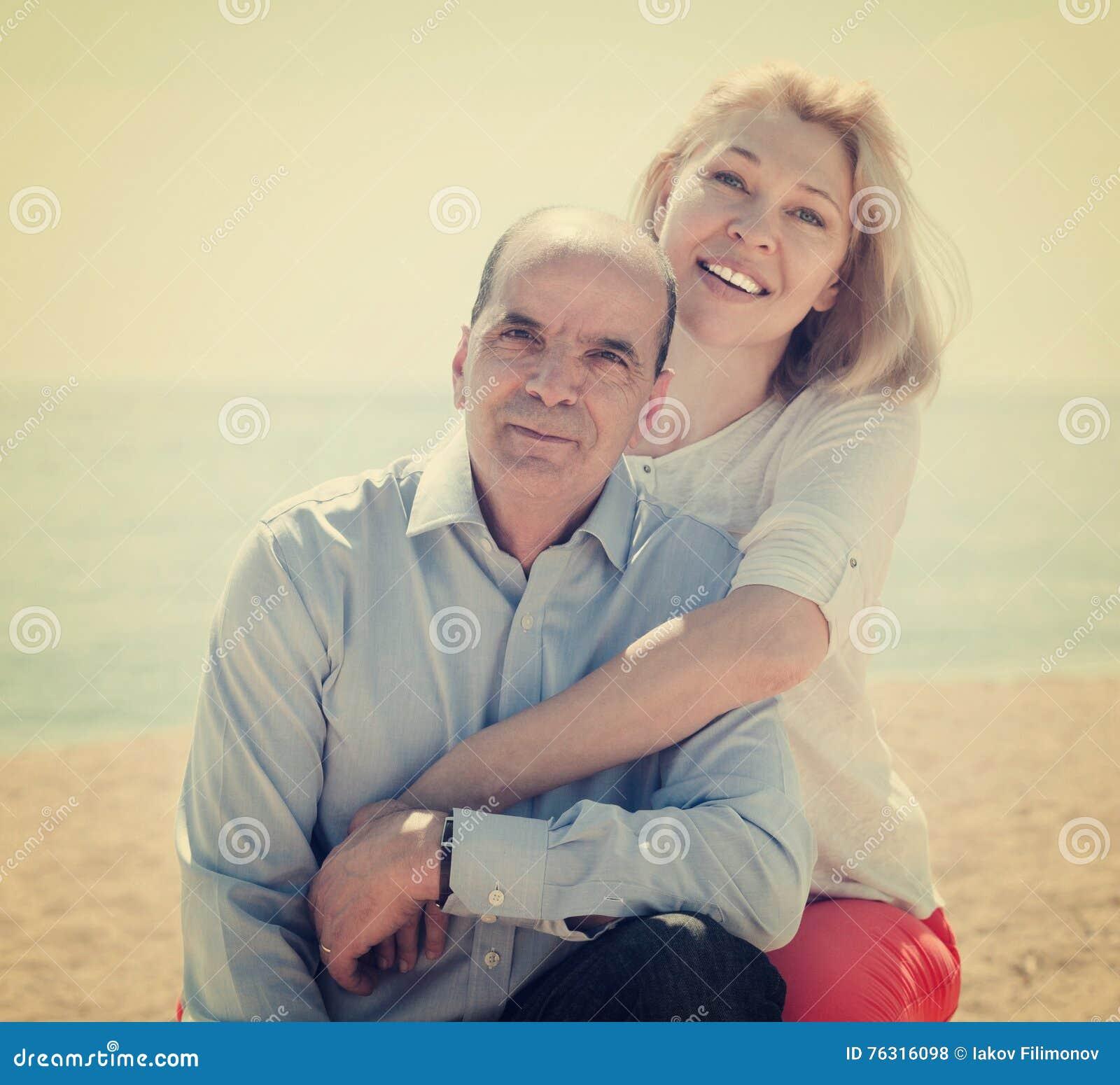 Homme supérieur et femme mûre contre la mer en été