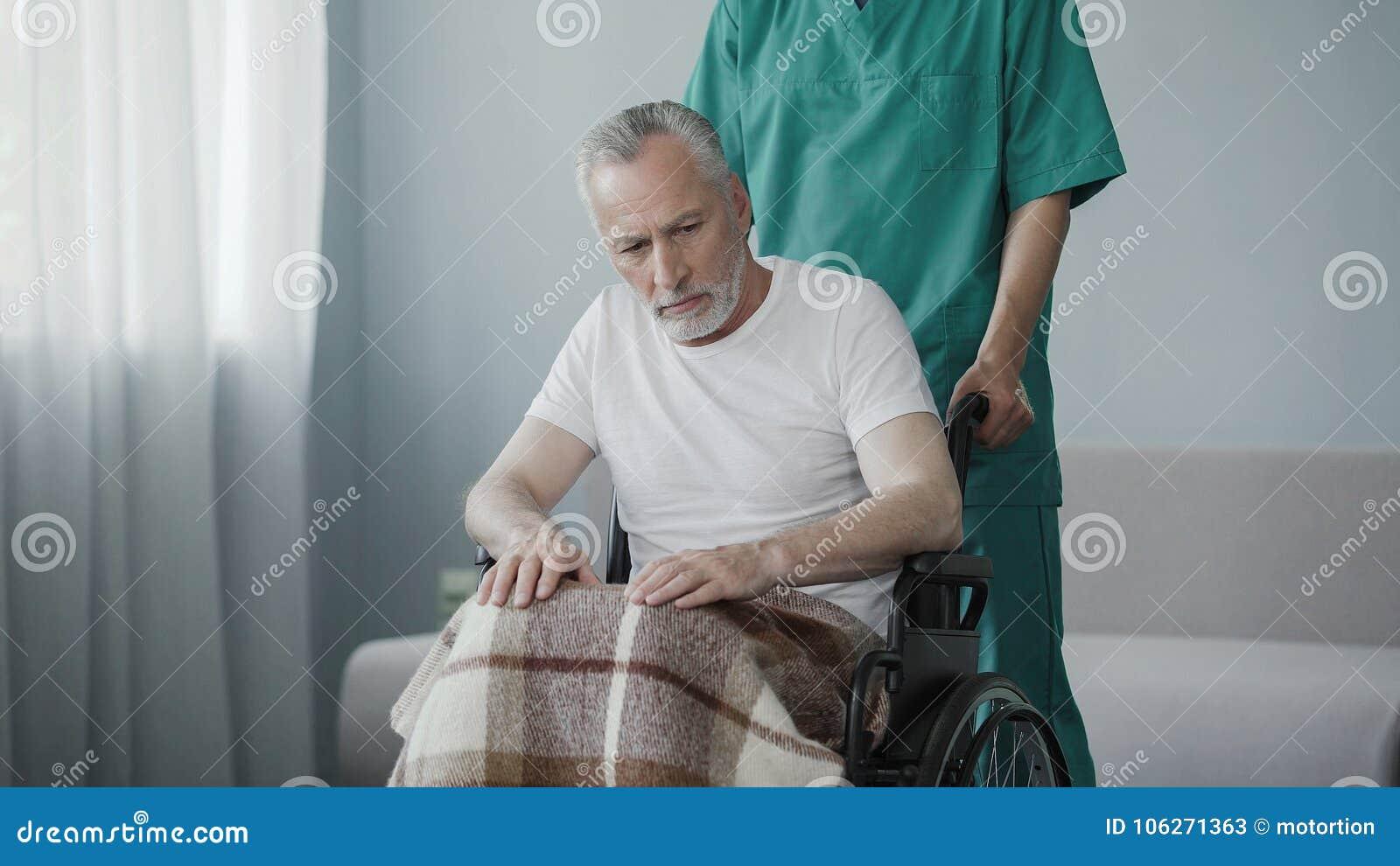 Homme supérieur handicapé s asseyant dans le fauteuil roulant, patiente de soutien d infirmière masculine