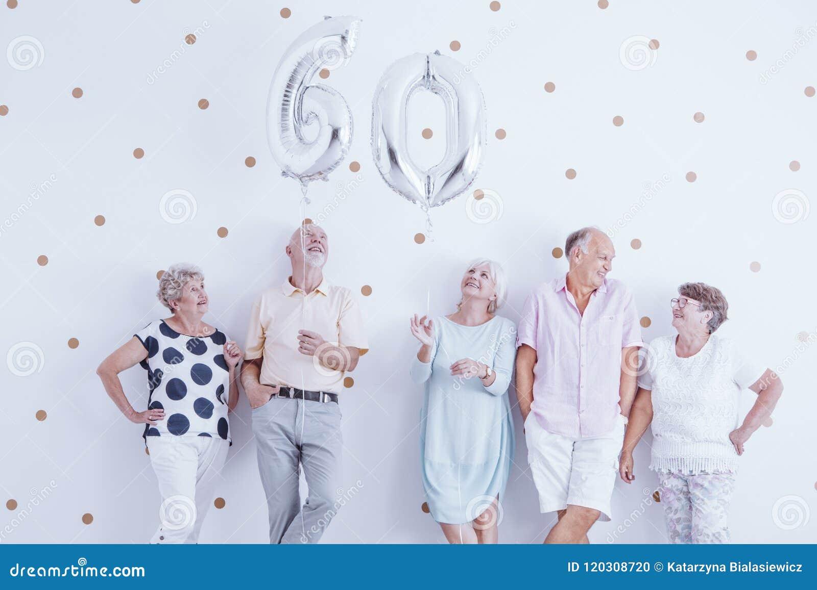 Homme supérieur heureux et femme tenant les ballons argentés