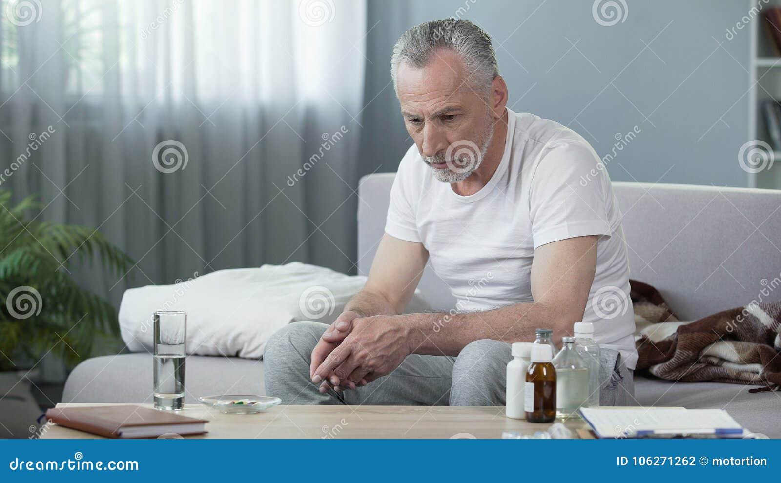 Homme supérieur malade seul s asseyant sur le divan et pensant à la vie, dépression
