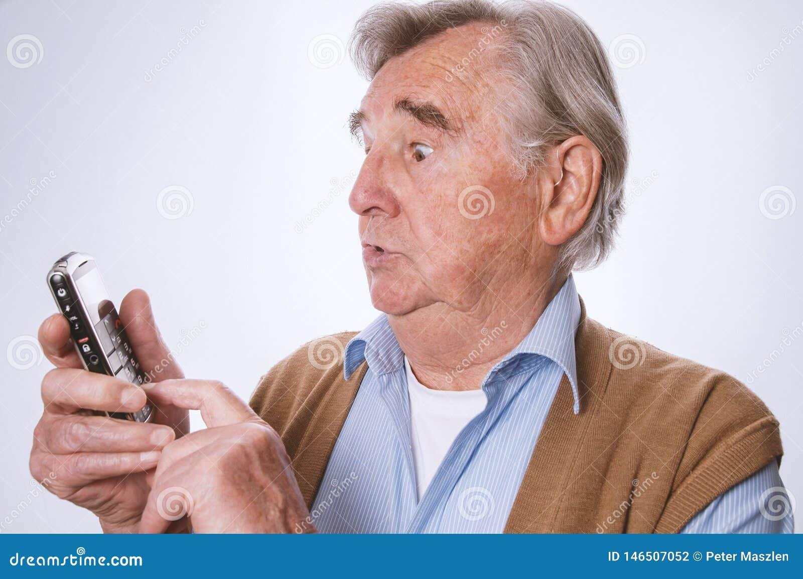 Homme supérieur semblant étonné et employant son mobilphone